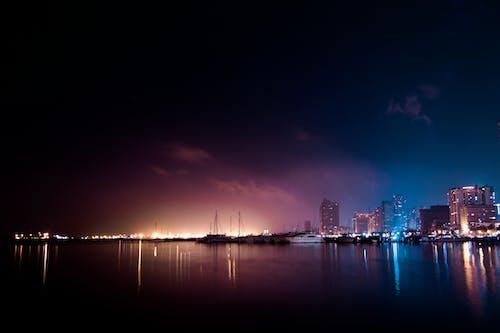 Безкоштовне стокове фото на тему «будівлі, вогні міста, вода, місто»