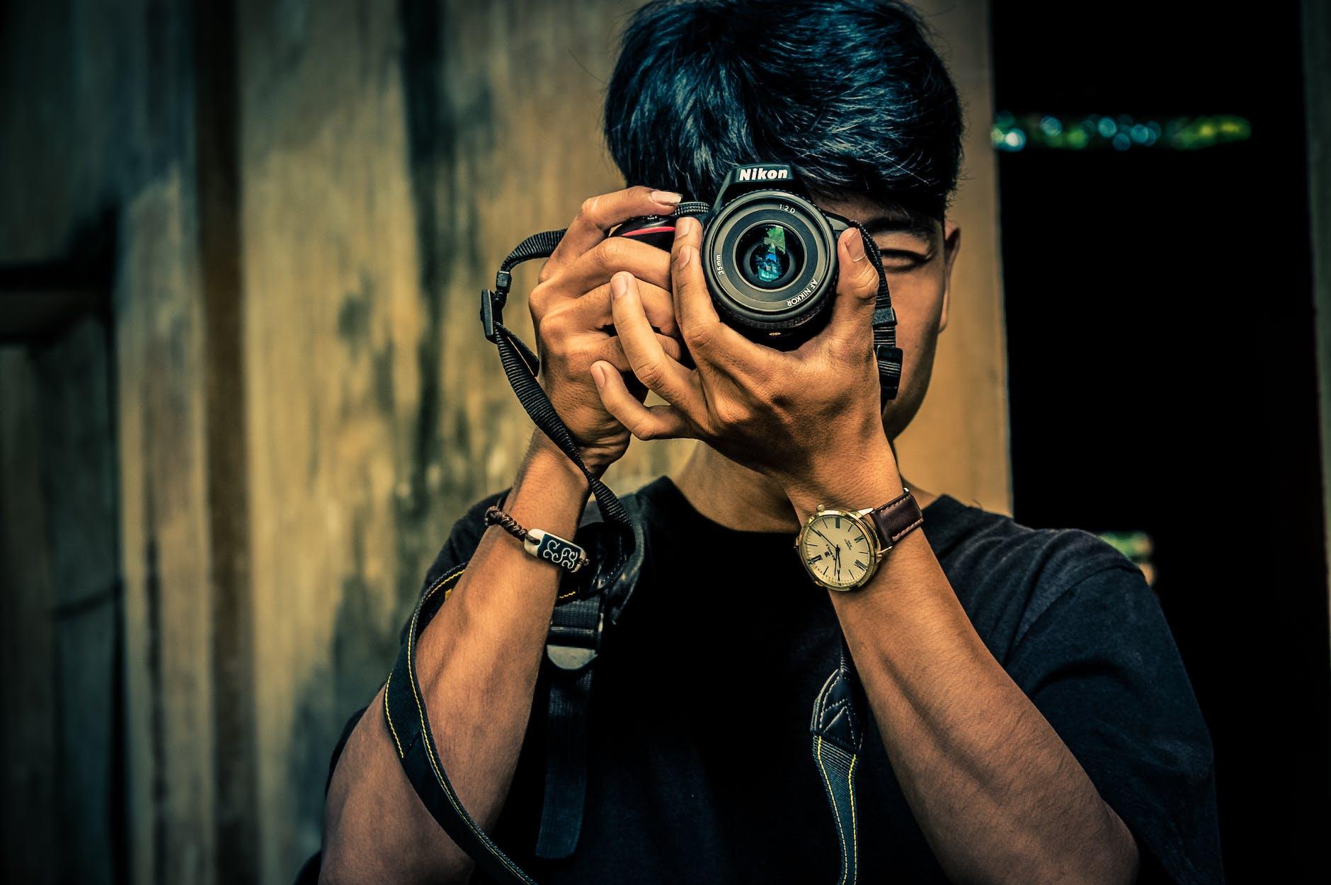 Man holding a nikon d5600 camera and capturing photo