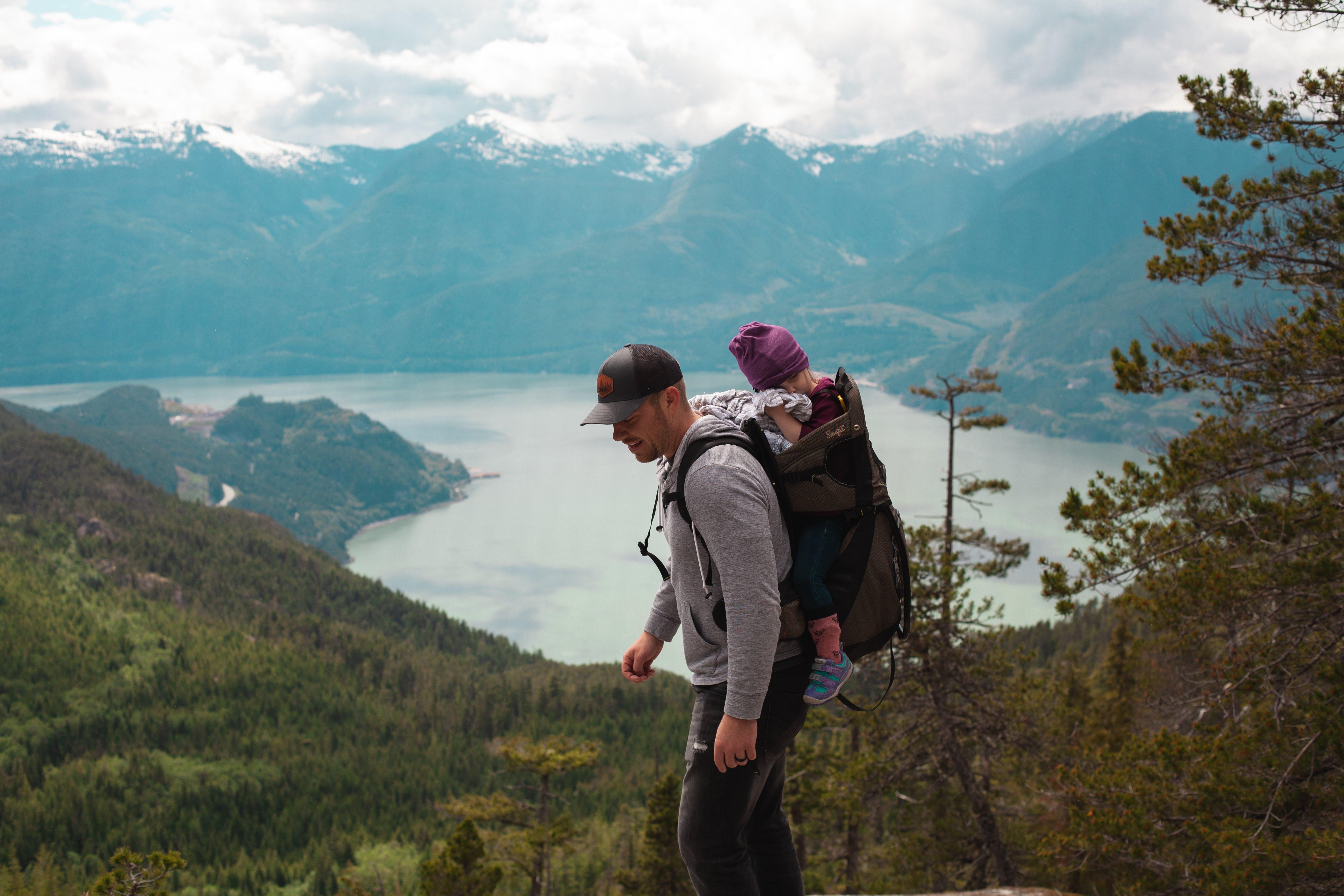Man Carrying Baby Near Lake
