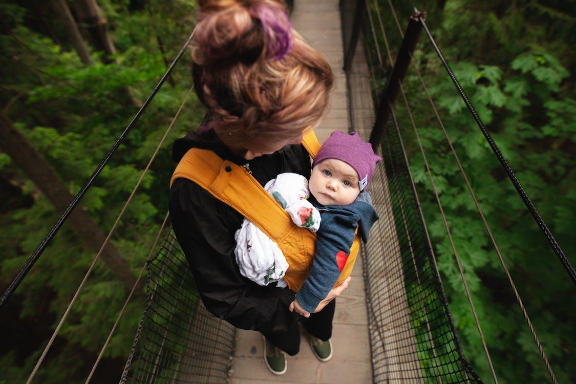 橋の上で赤ちゃんを運ぶ女性