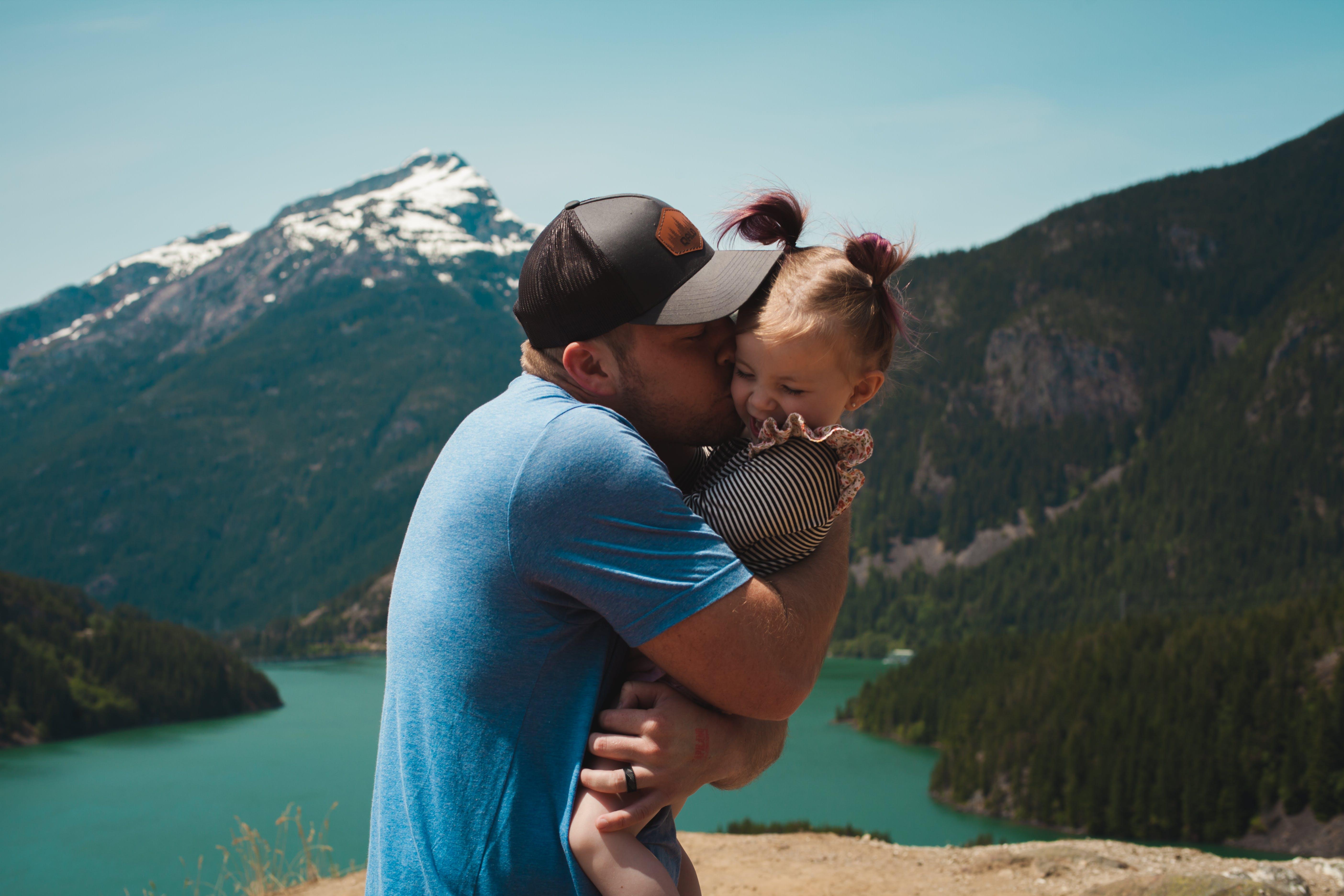 Man Wearing Blue Crew-neck T-shirt Holding Girl Near Mountains