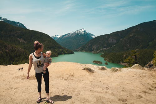 Woman Wearing Grey Tank Top Carrying Baby in Distant of Lake Between Mountains