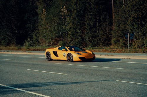 Shallow Focus Photography of Orange Sportcar on Asphalt Road