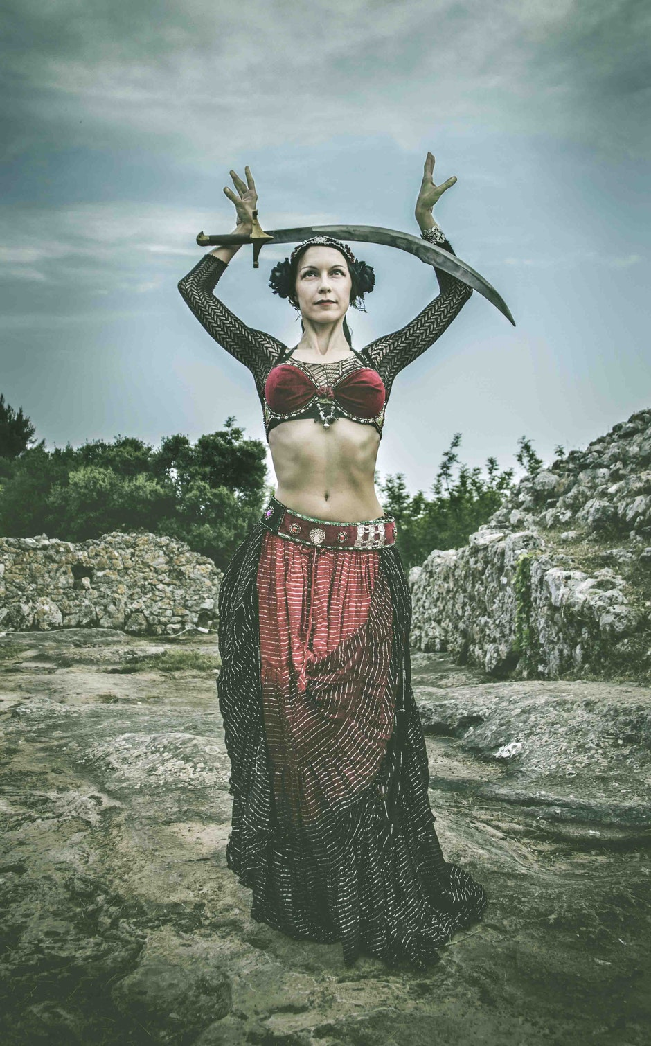 Woman Wearing Black and Red Dress Holding Sword Standing on Rock Surface during Day Time