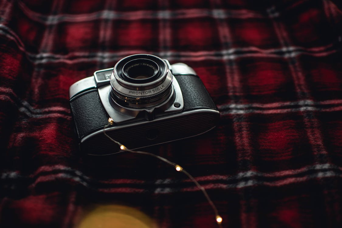 Black and Gray Point-and-shoot Camera on Red, Black, and White Plaid Textile