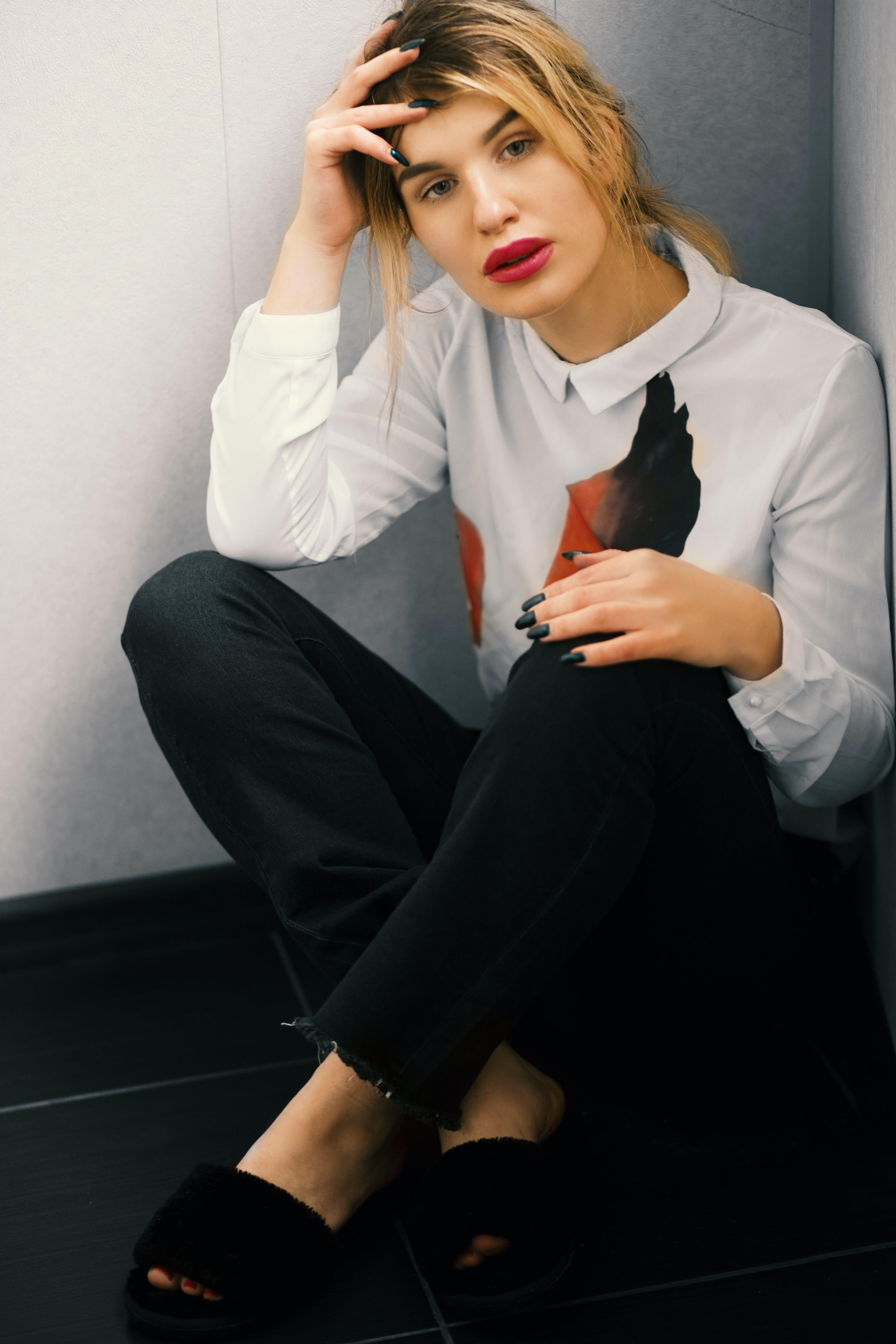 Women Wearing Black Dress Pants and White Long-sleeved Dress Shirt Sitting on the Corner