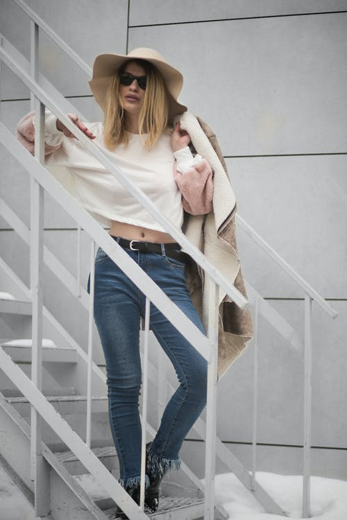 Woman in White Crew-neck Long-sleeved Crop Top and Blue Denim Fitted Jeans Outfit Standing on White Metal Stairs Beside White Wall at Daytimne