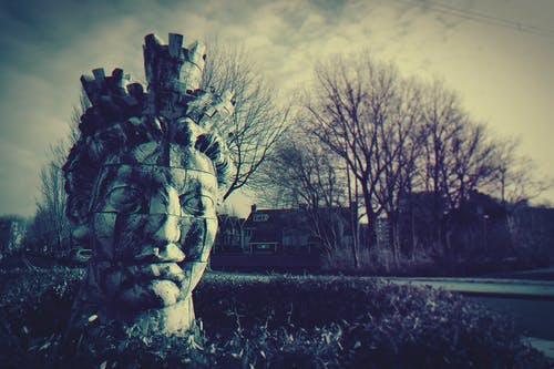 Human Head Statue Near Bare Trees