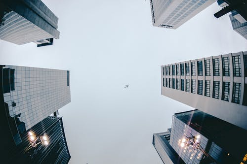 Low Angle Photography of Airplane Flying Above High Rise Buildings