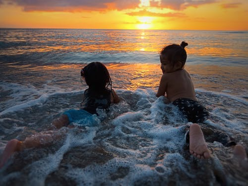 Photo of Two Girls in Beach during Golden Hour