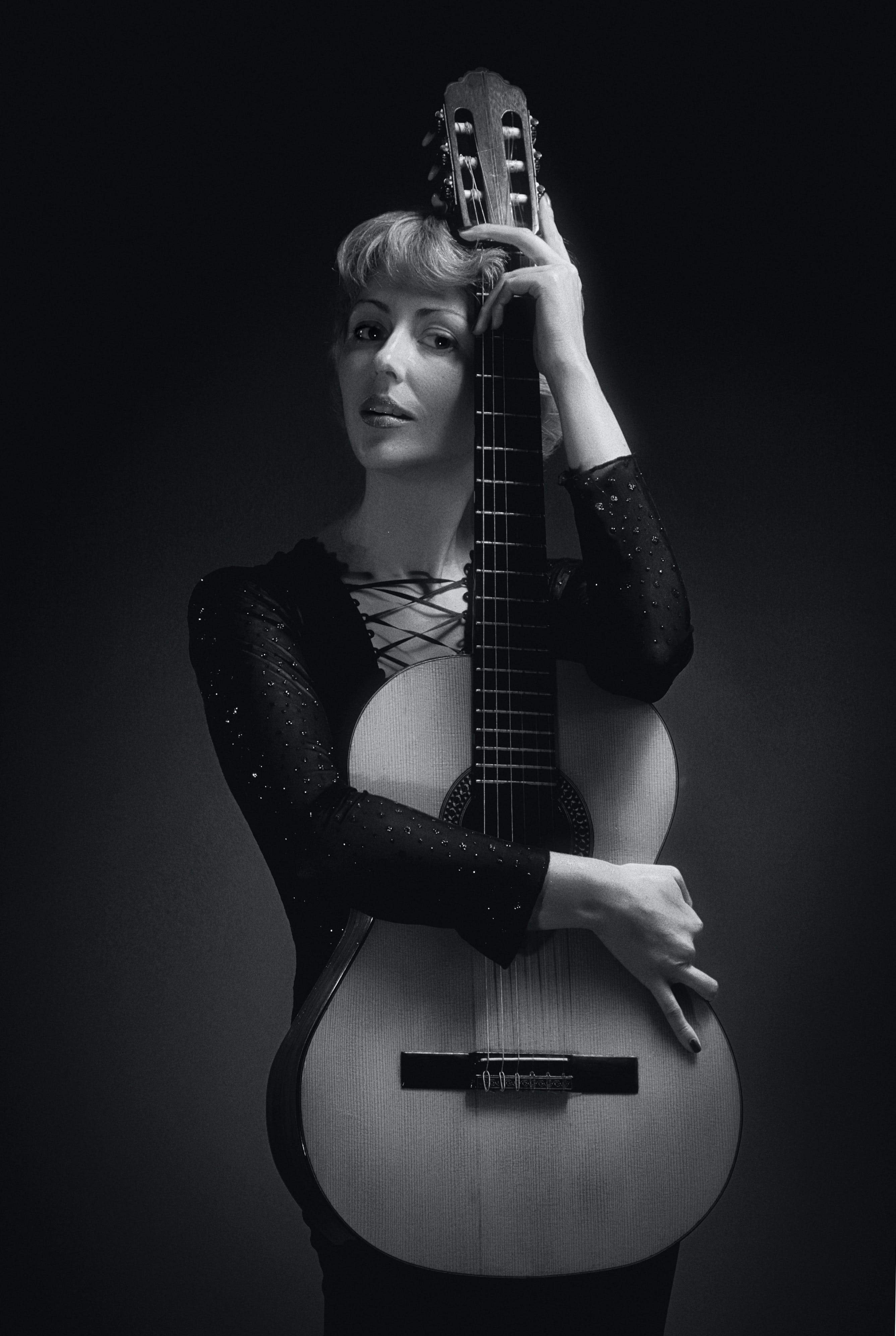 Woman in Black Long-sleeved Dress Holding Classical Guitar