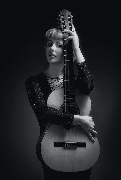 拿著古典吉他的黑色長袖連衣裙的女人