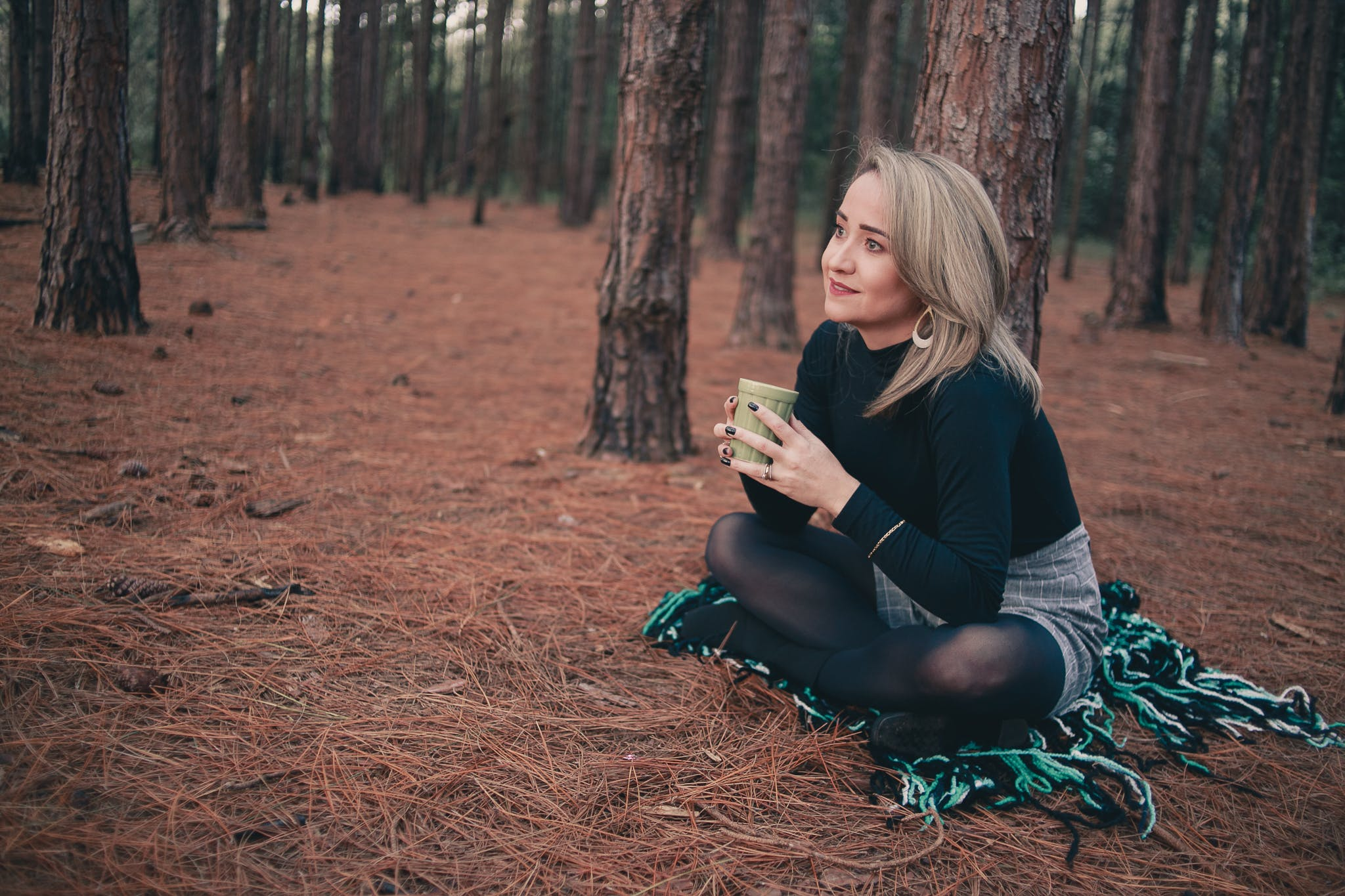 Woman in Black Sweater Sitting on Brown Ground While Holding Cup