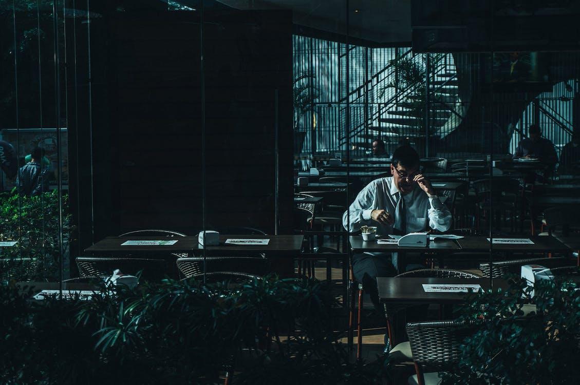 Man Seating Beside Desk Near Door