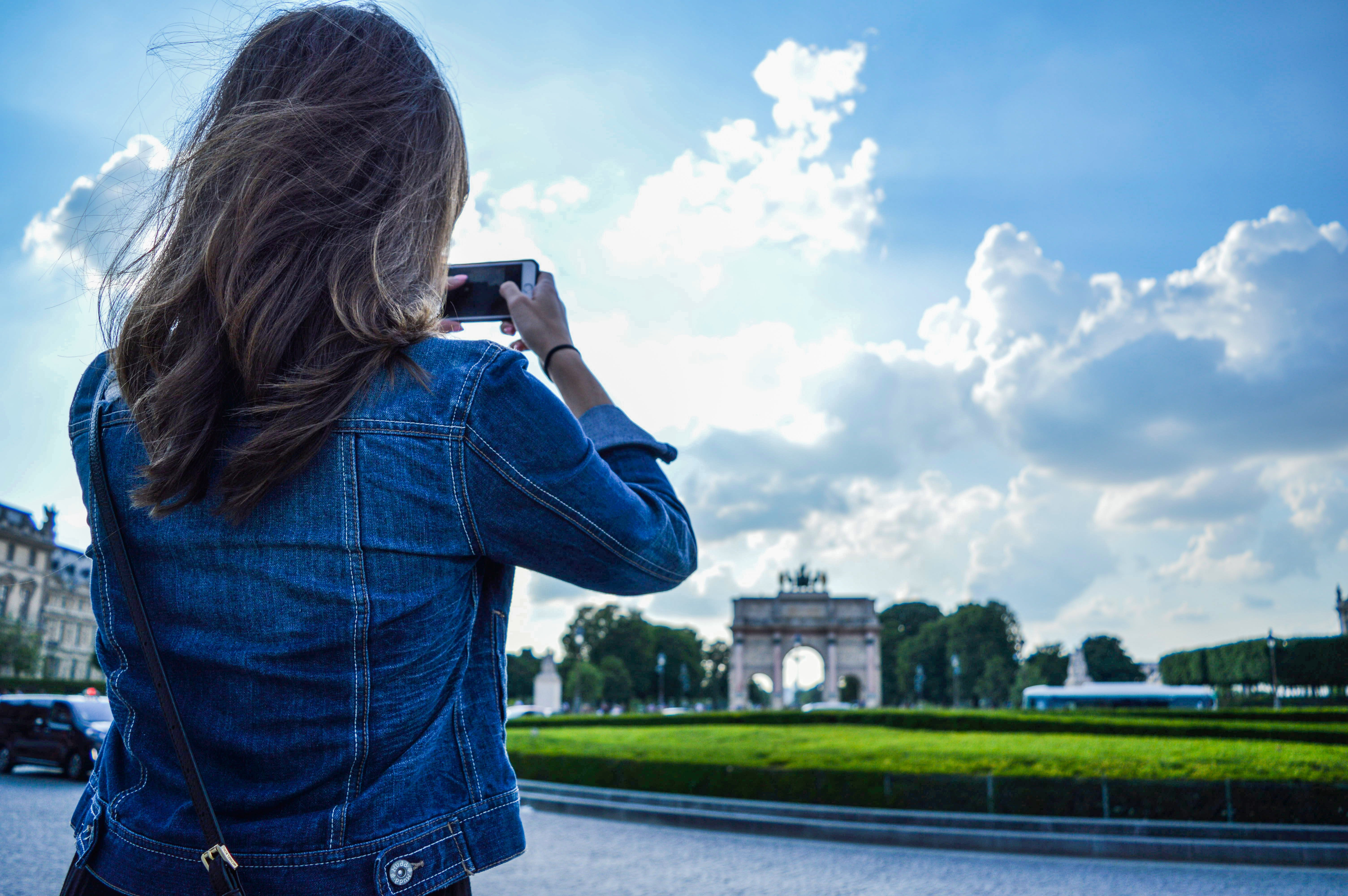 Woman Wearing Blue Denim Jacket Standing While Holding Smartphone