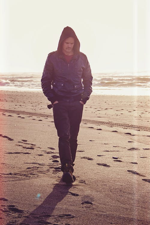 Man Walking on Beach Wearing Black Leather Coat