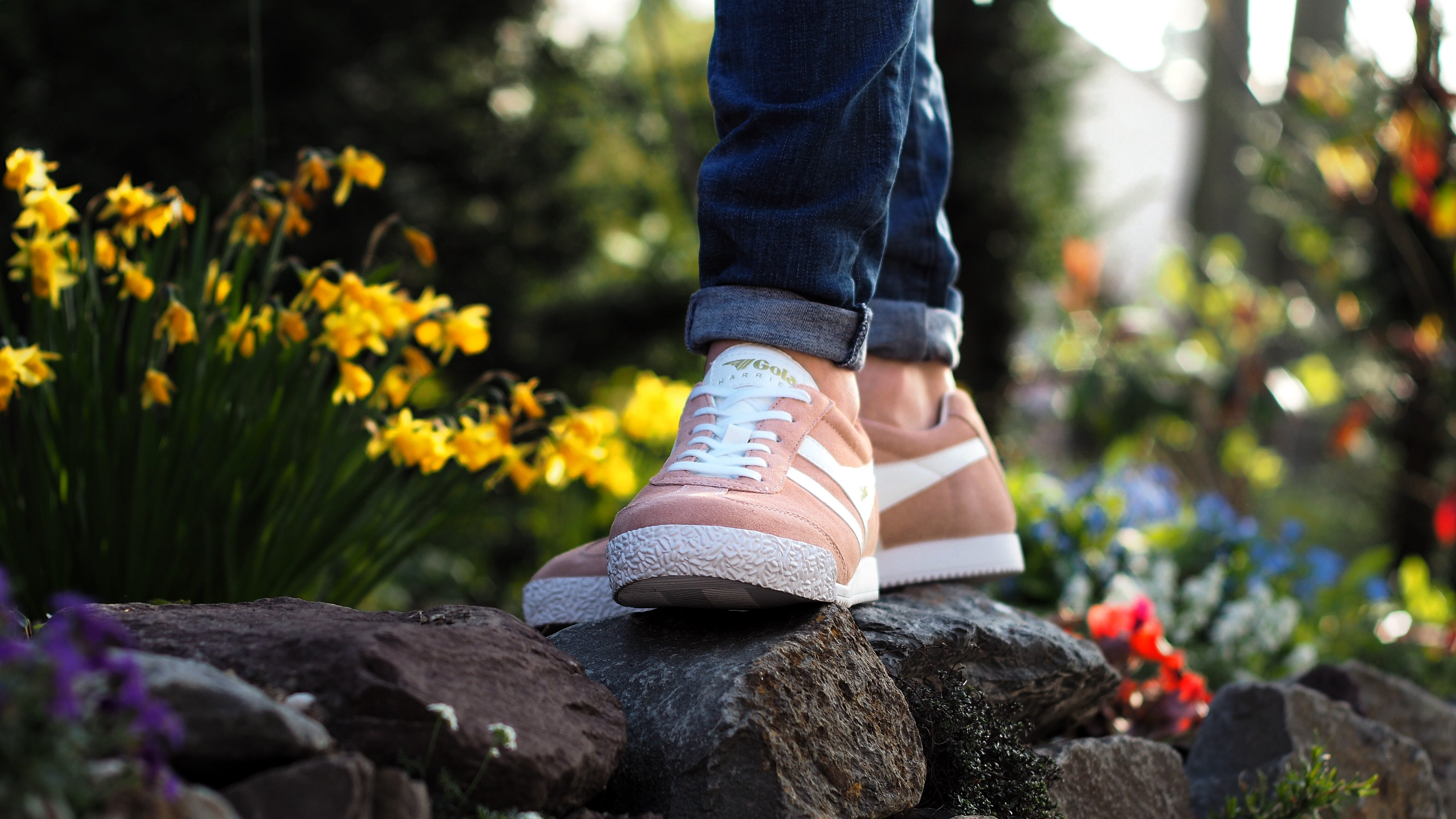 Person Wearing Pink Nike Low-top Sneakers Stepping on Stone Surrounded by Flower
