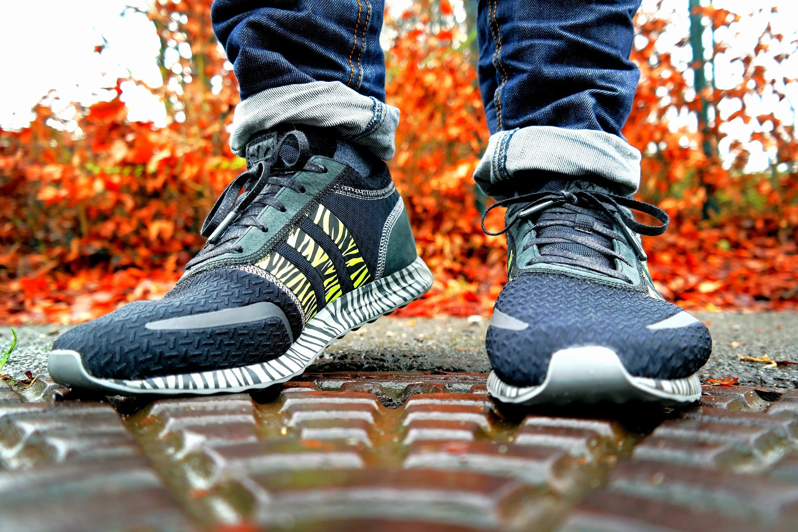 Shallow Focus Photography of Pair of Black Black-and-white Adidas Running Shoes