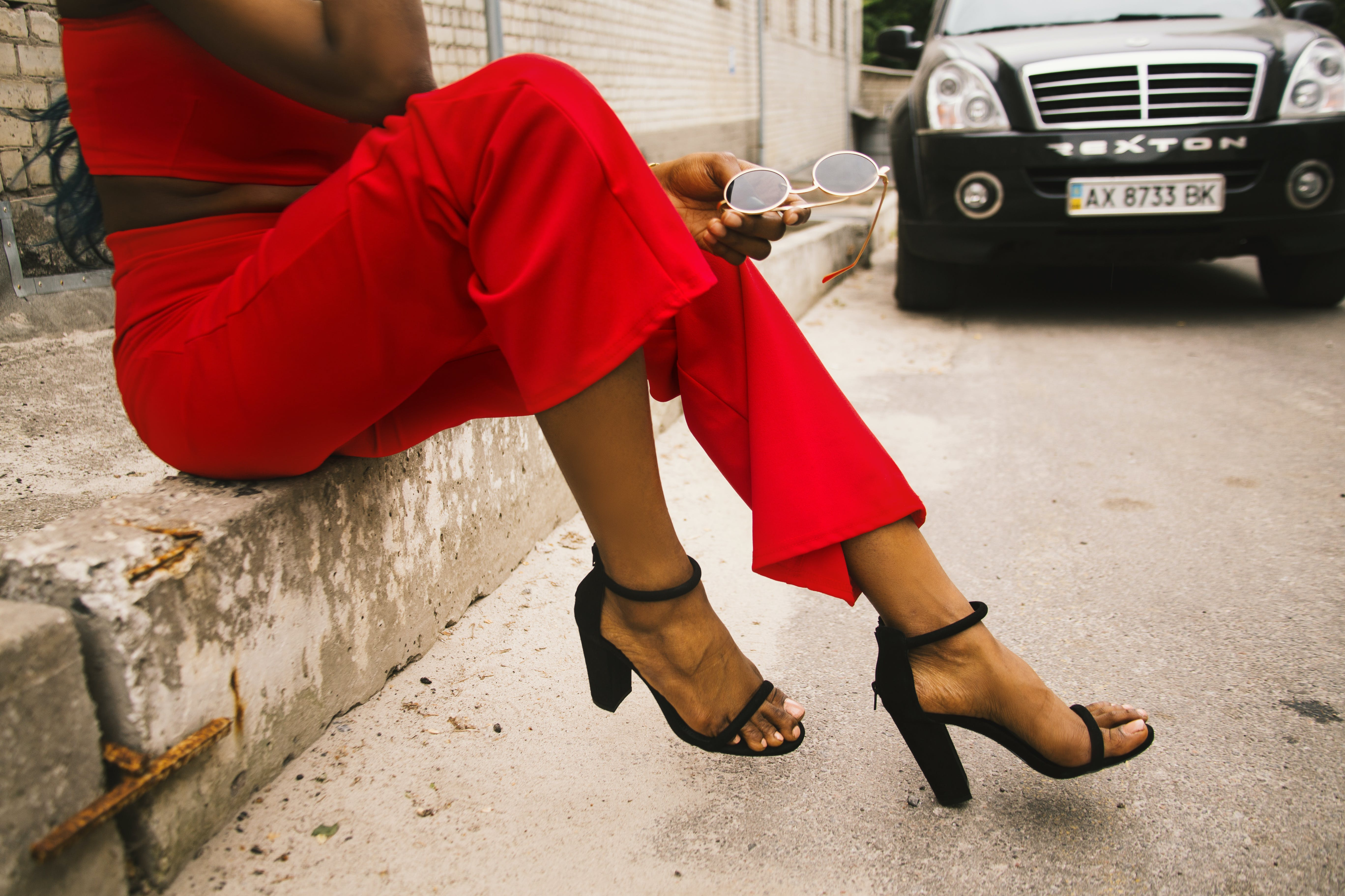 Woman Wearing Red Pants and Black Leather Ankle Strap Sandals