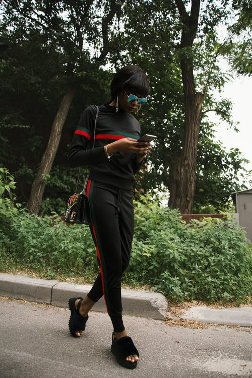 Woman in Black, Green, and Red Gucci Sweatshirt and Sweatpants Using Smartphone