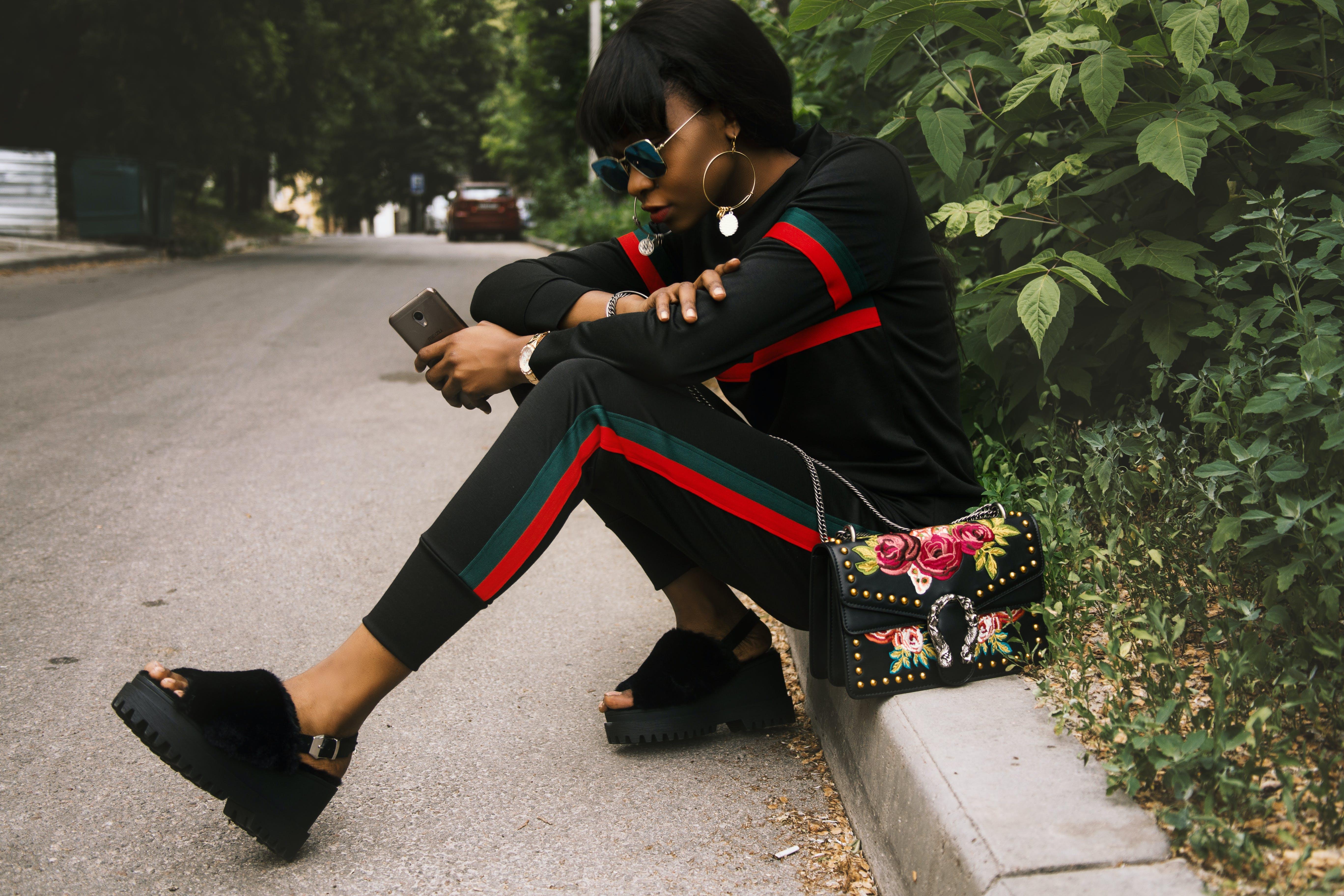 Woman Sitting on Gray Concrete Sidewalk Taken