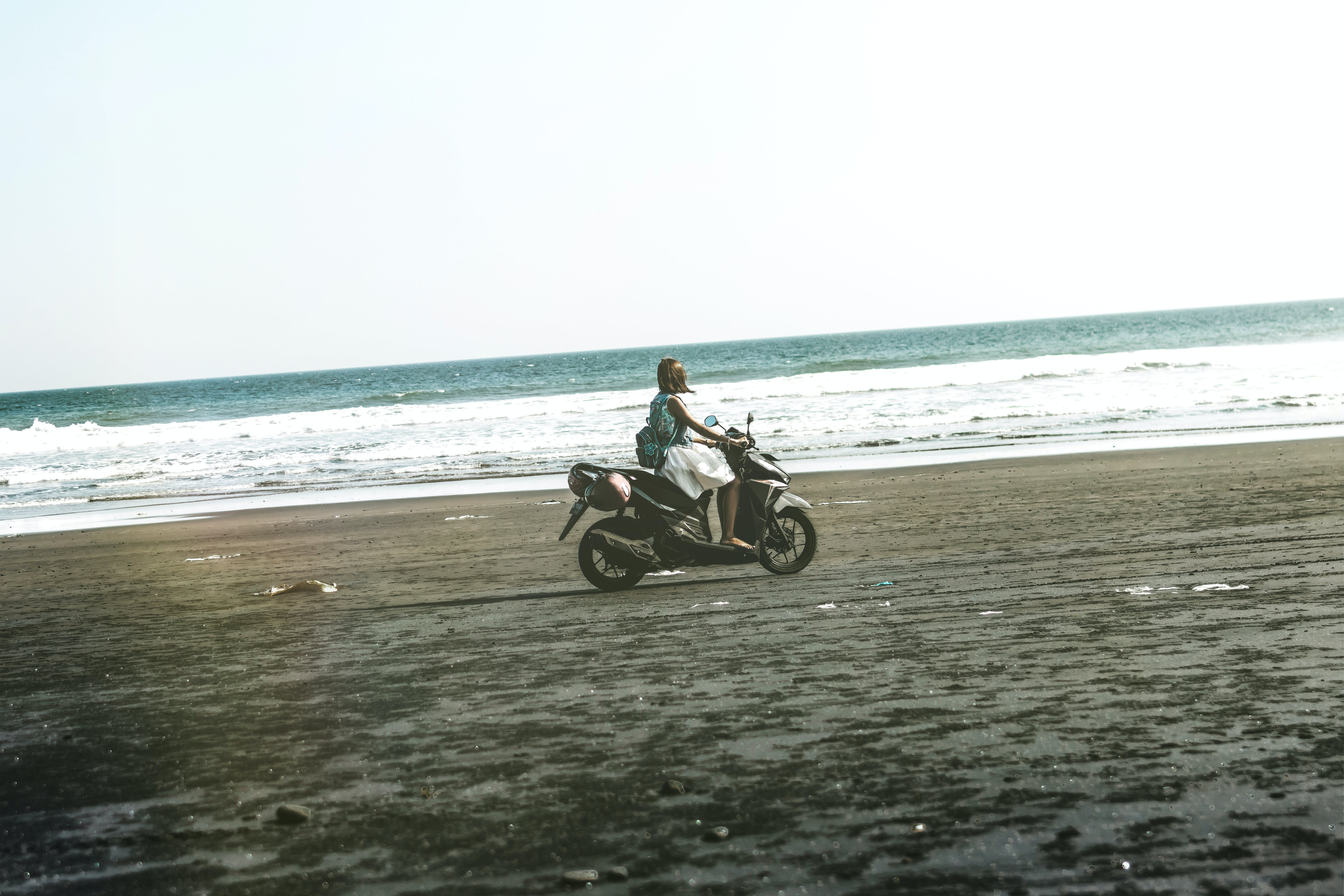 Woman Riding Black and Gray Motor Scooter on Beach
