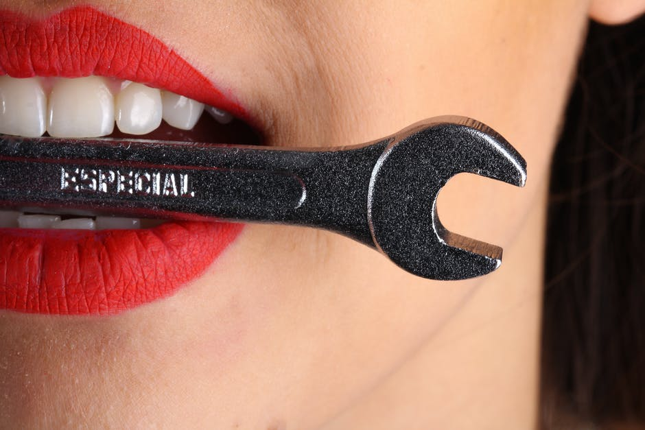 Close View of Woman With Red Lips Biting Gray Special Wrench