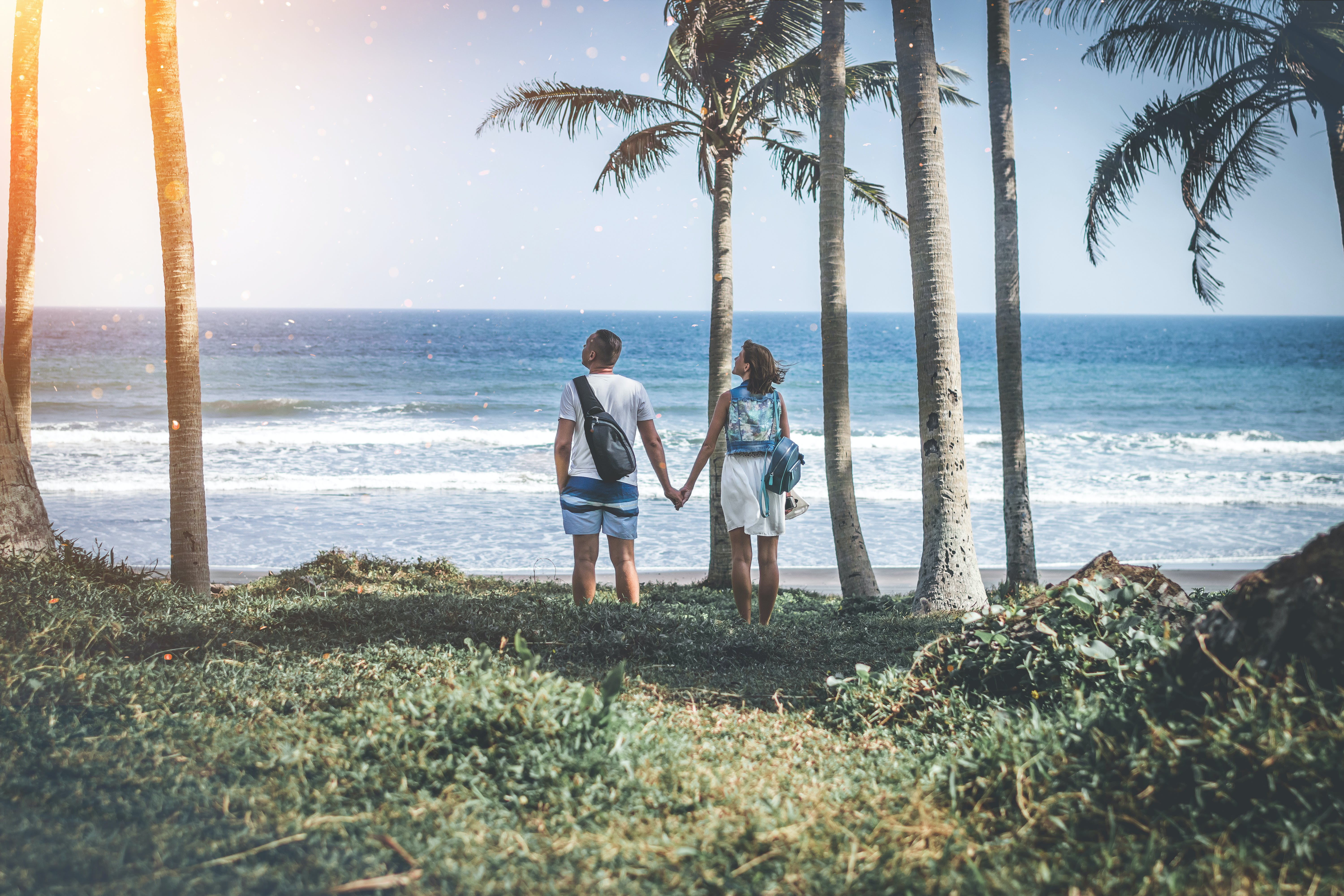 Man and Woman Holding Hand Near Beach Shore Under Sunny Sky