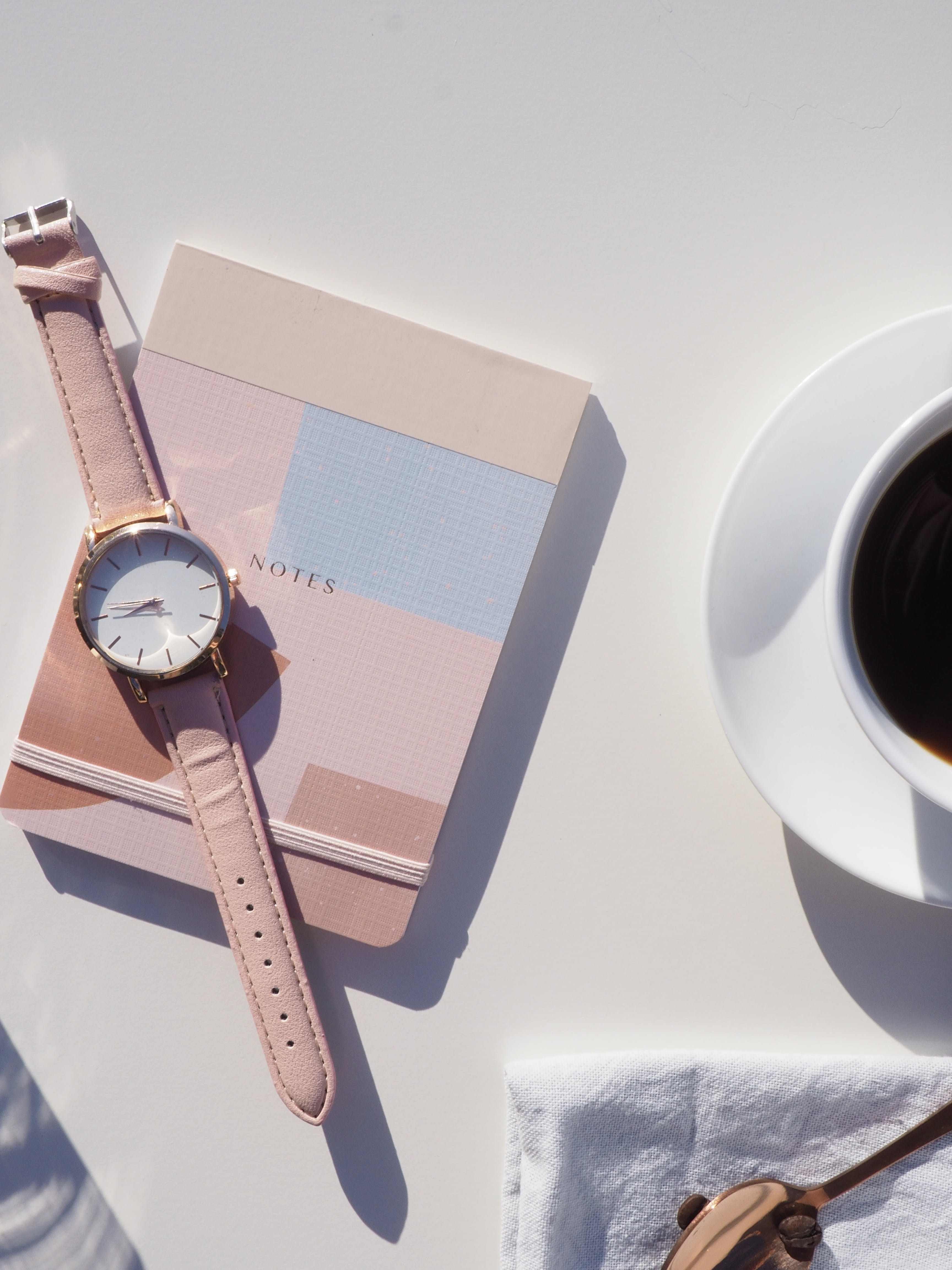 Round Gold-colored Analog Watch With Pink Leather Strap on Pink Notebook