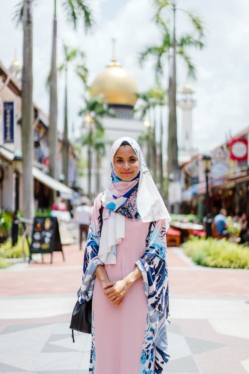 Woman Wearing Hijab and Abaya Dress While Standing With Mosque As Background