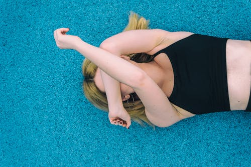 Woman Wearing Black Sports Brassiered Lying on Teal Surface While Covering Her Face With Her Arms