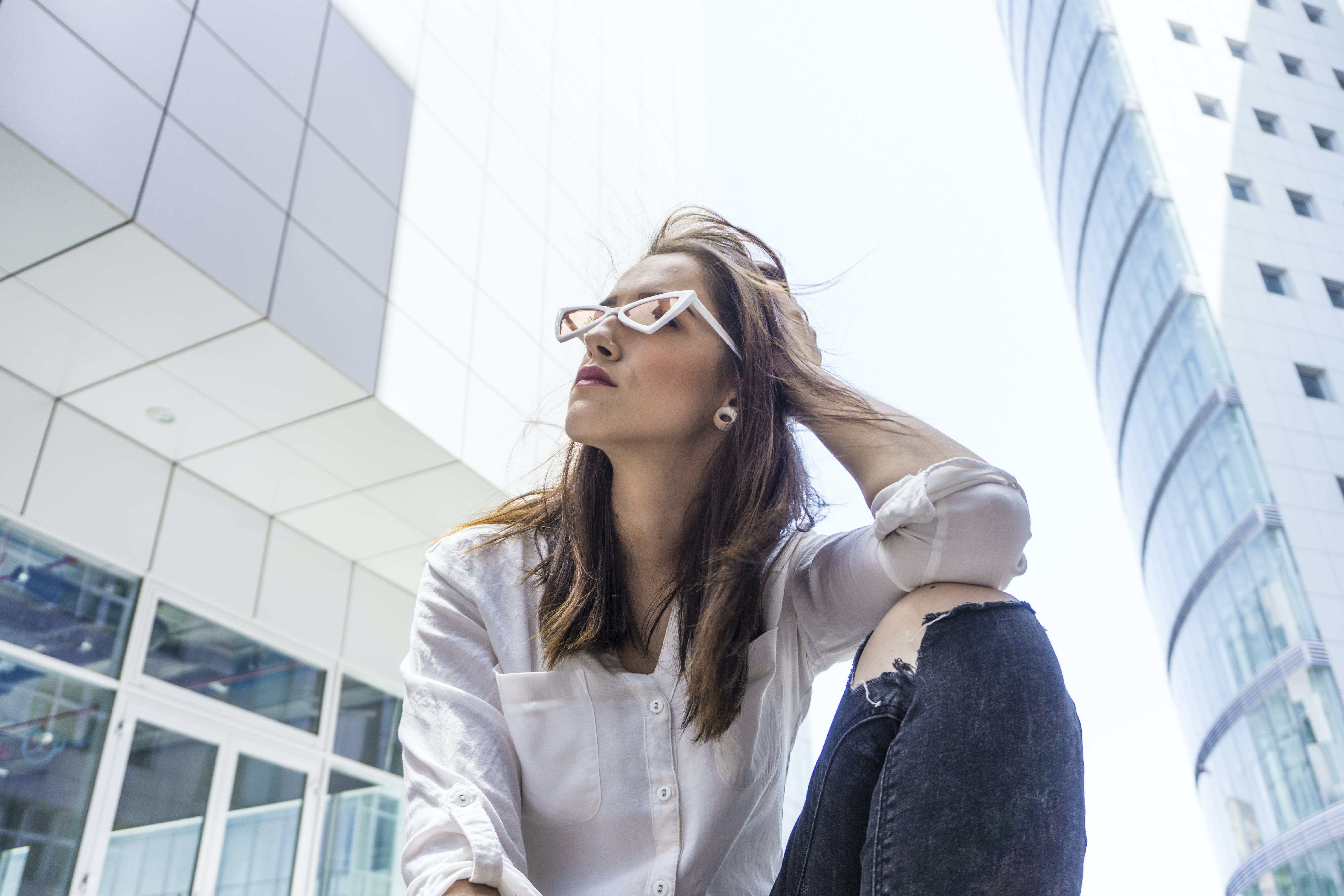 Low Angle Photography of Woman in White Shirt Sitting Beside Buildings