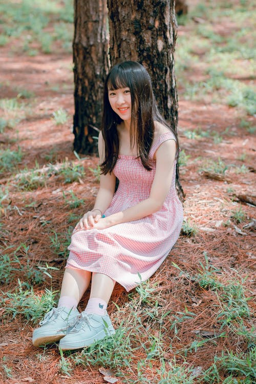 Girl's Pink Sleeveless Dress Sits Beside Black Tree Trunk at Daytime