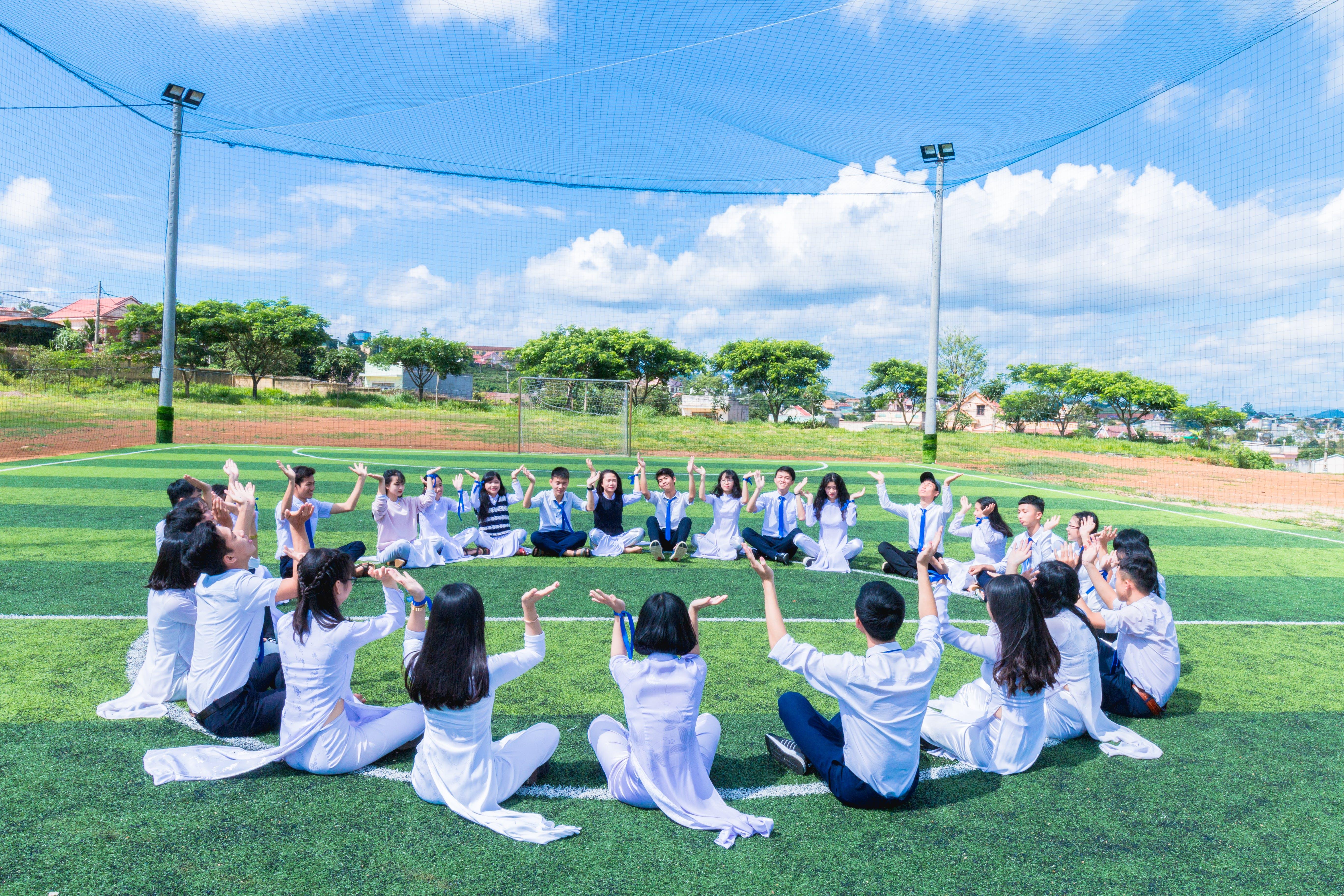 People Sitting on Green Grass Field