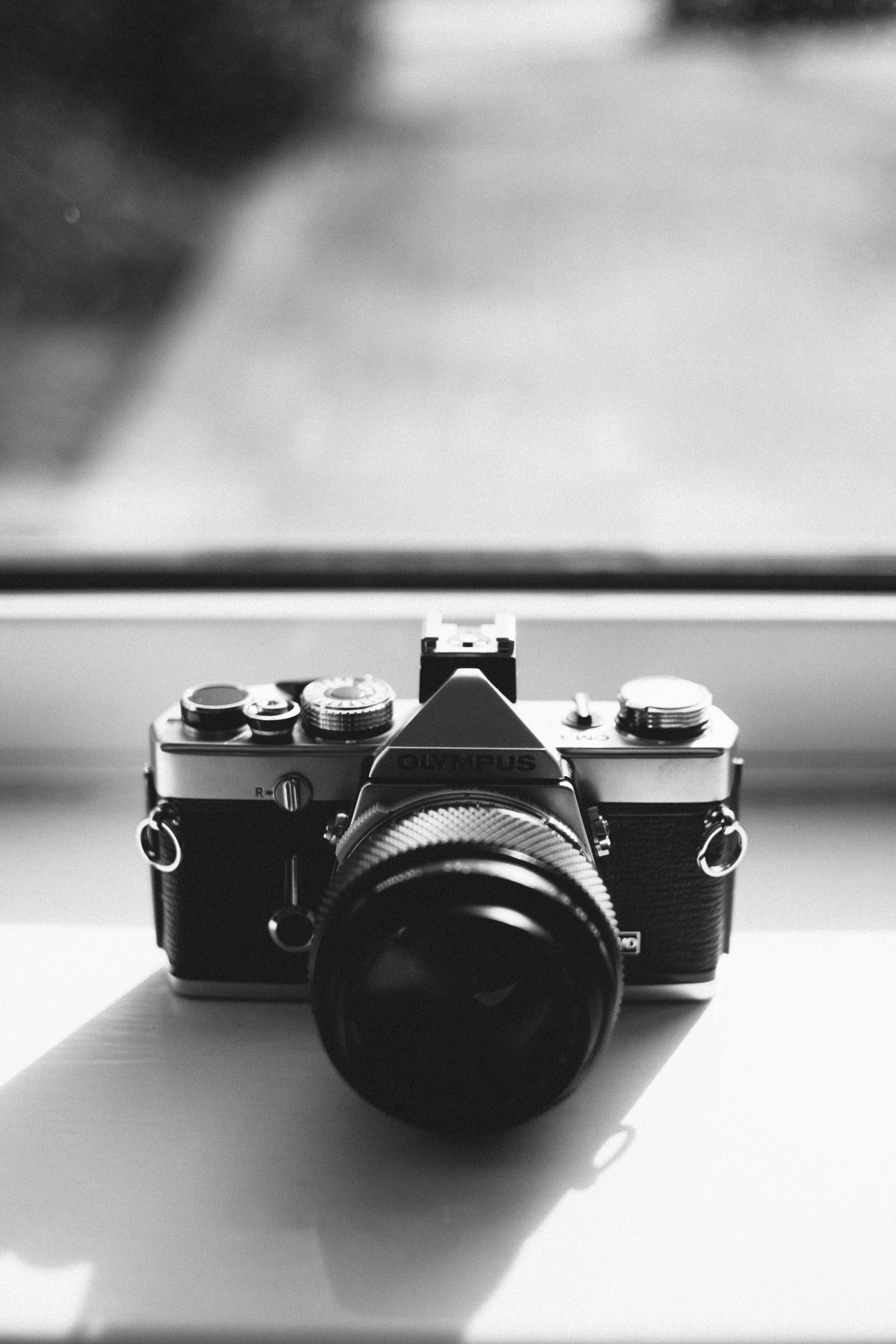 Grayscale Photography of Olympus Dslr Camera Near the Mirror