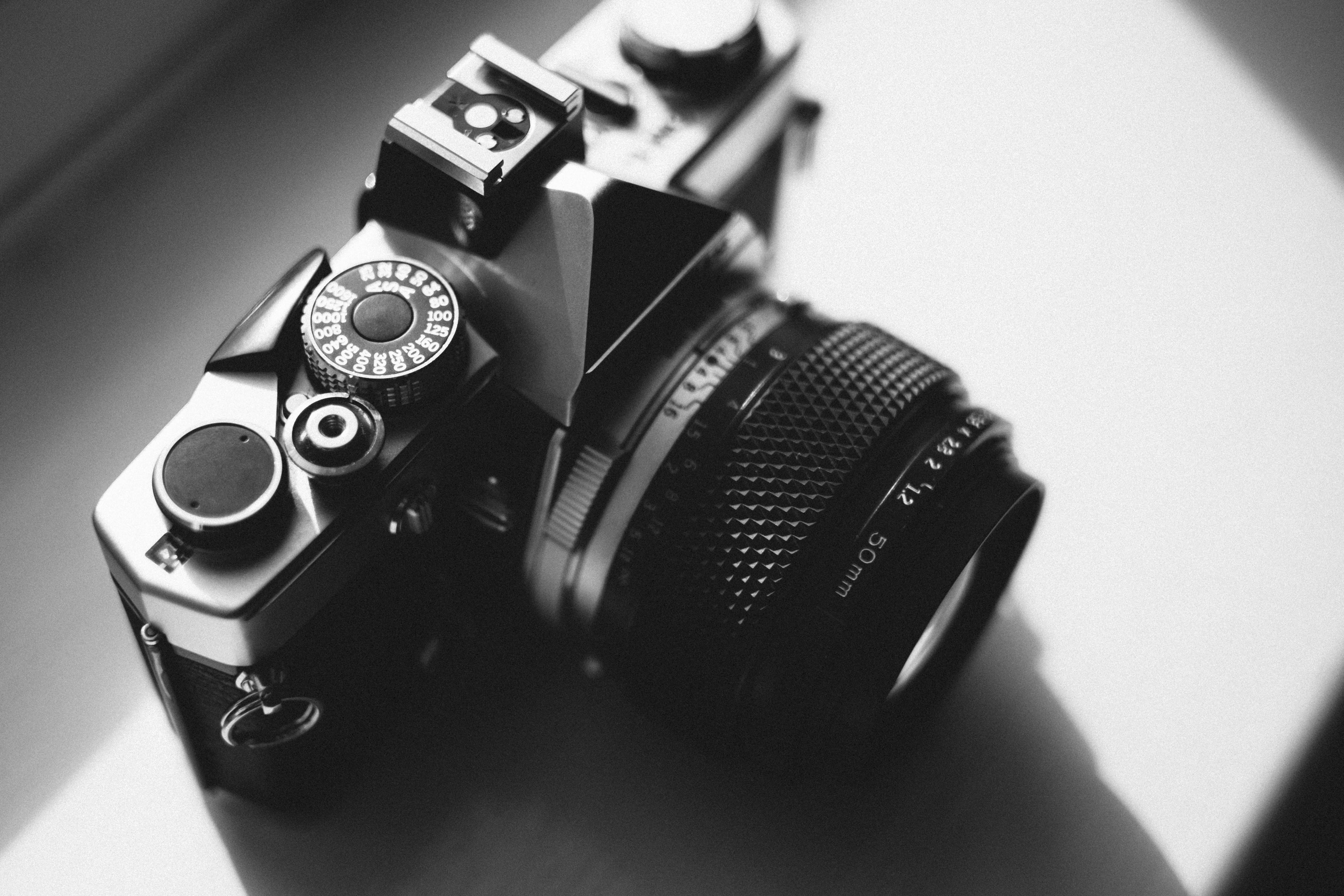 Black and Gray Dslr Camera on White Surface