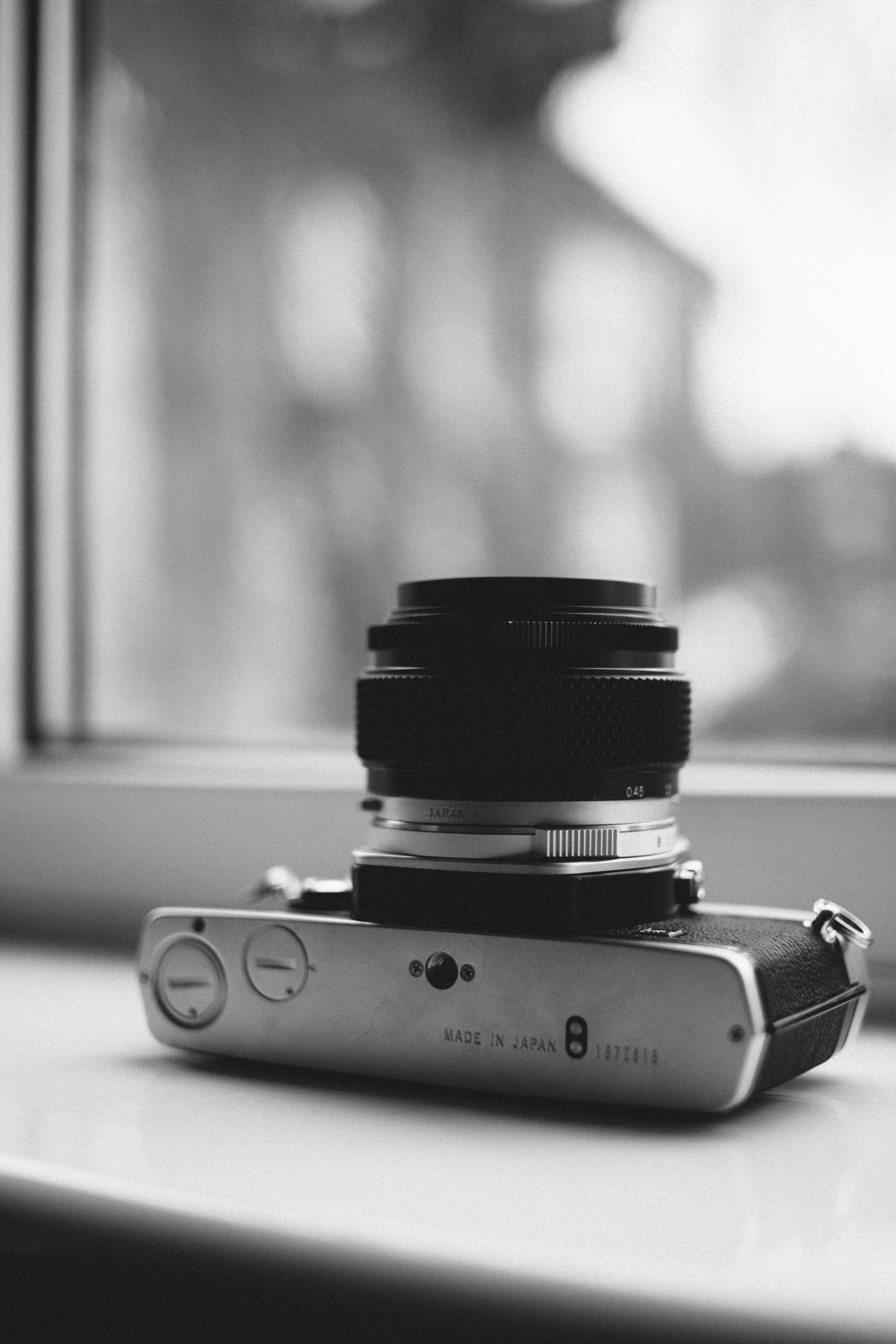 Grayscale Photography of Camera Near Window