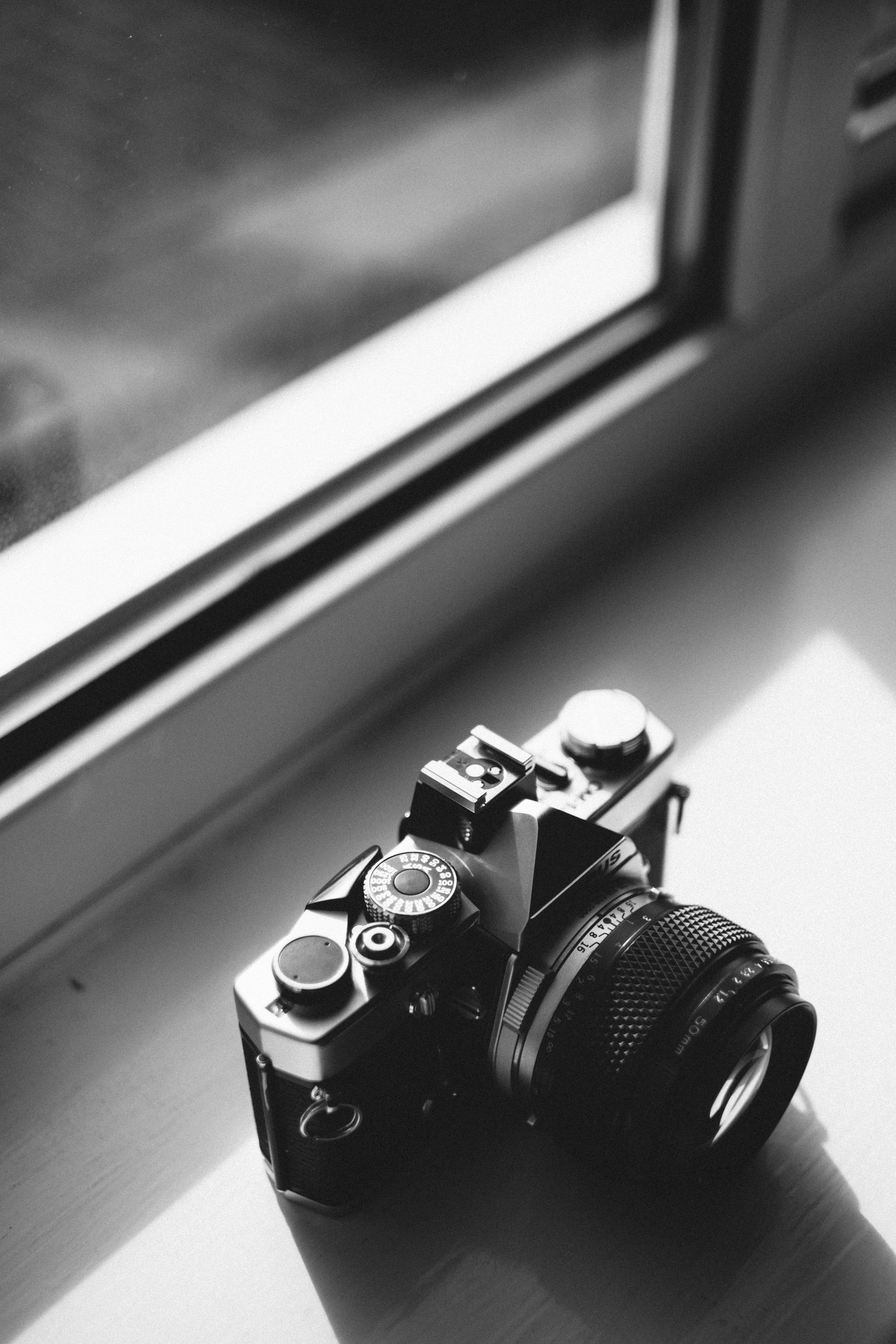 Grayscale Photo of Classical Camera Near Window