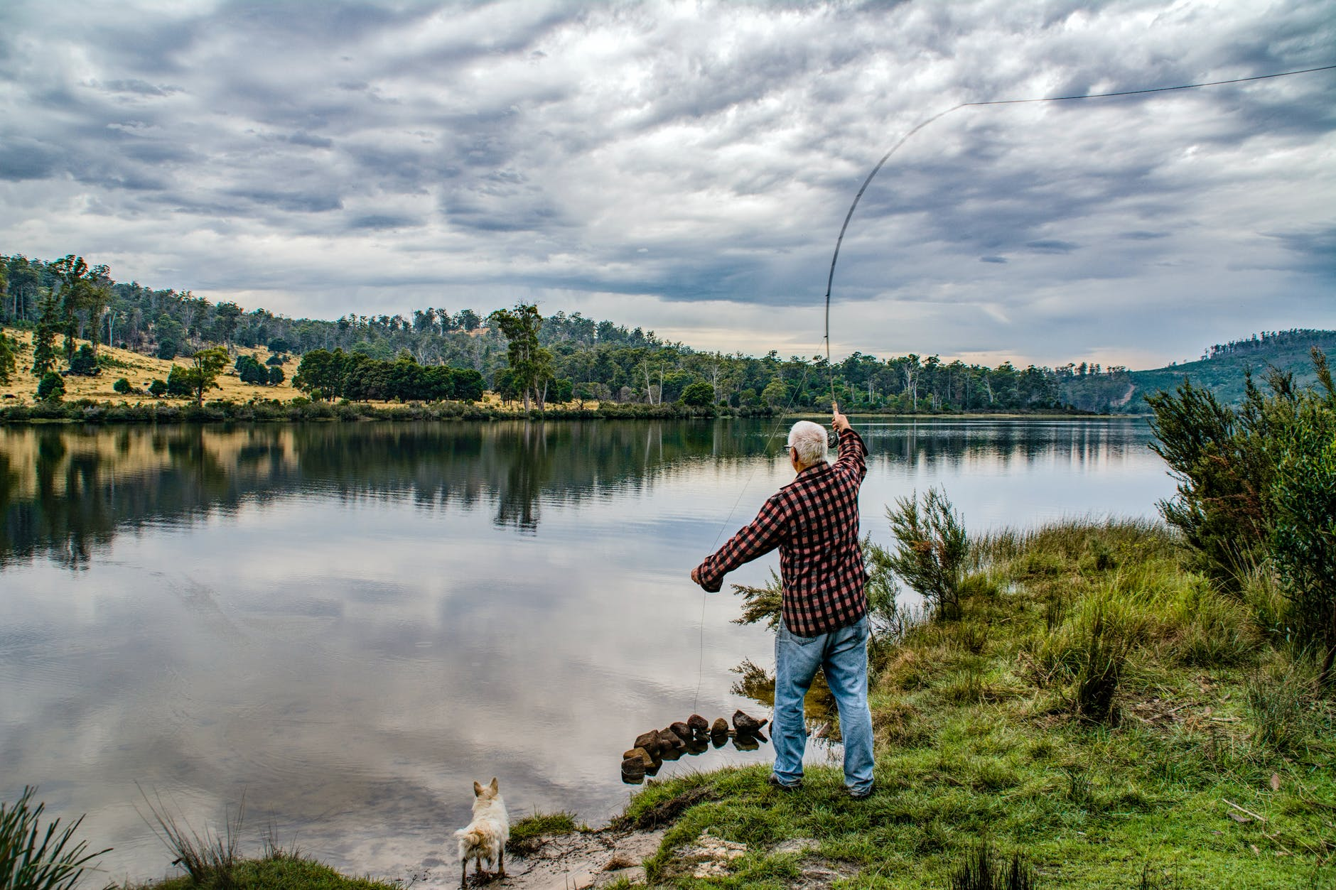 a man setting up his fishing rod on a riverbank