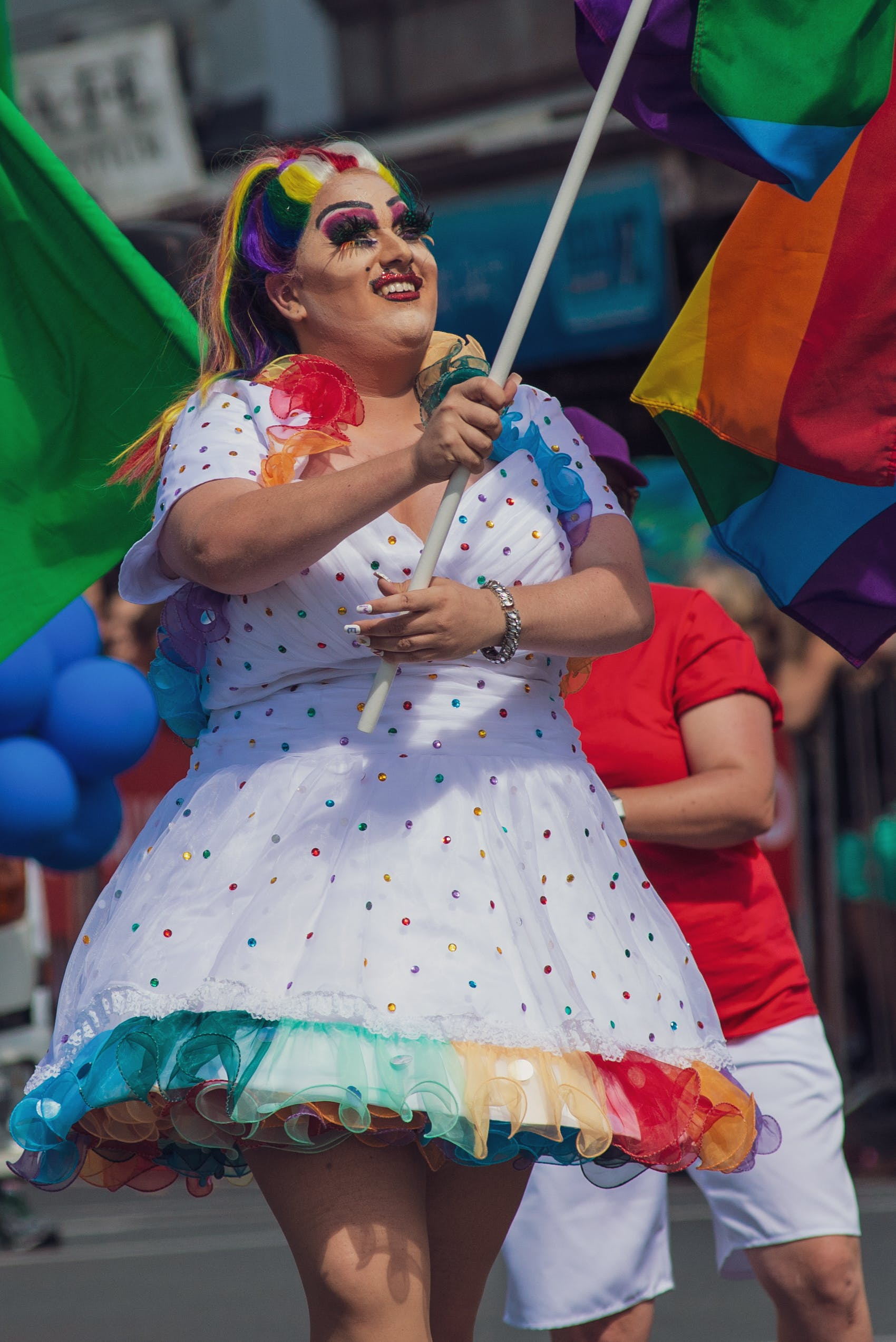 Woman in Multicolored Polka-dot Dress Holding Flag