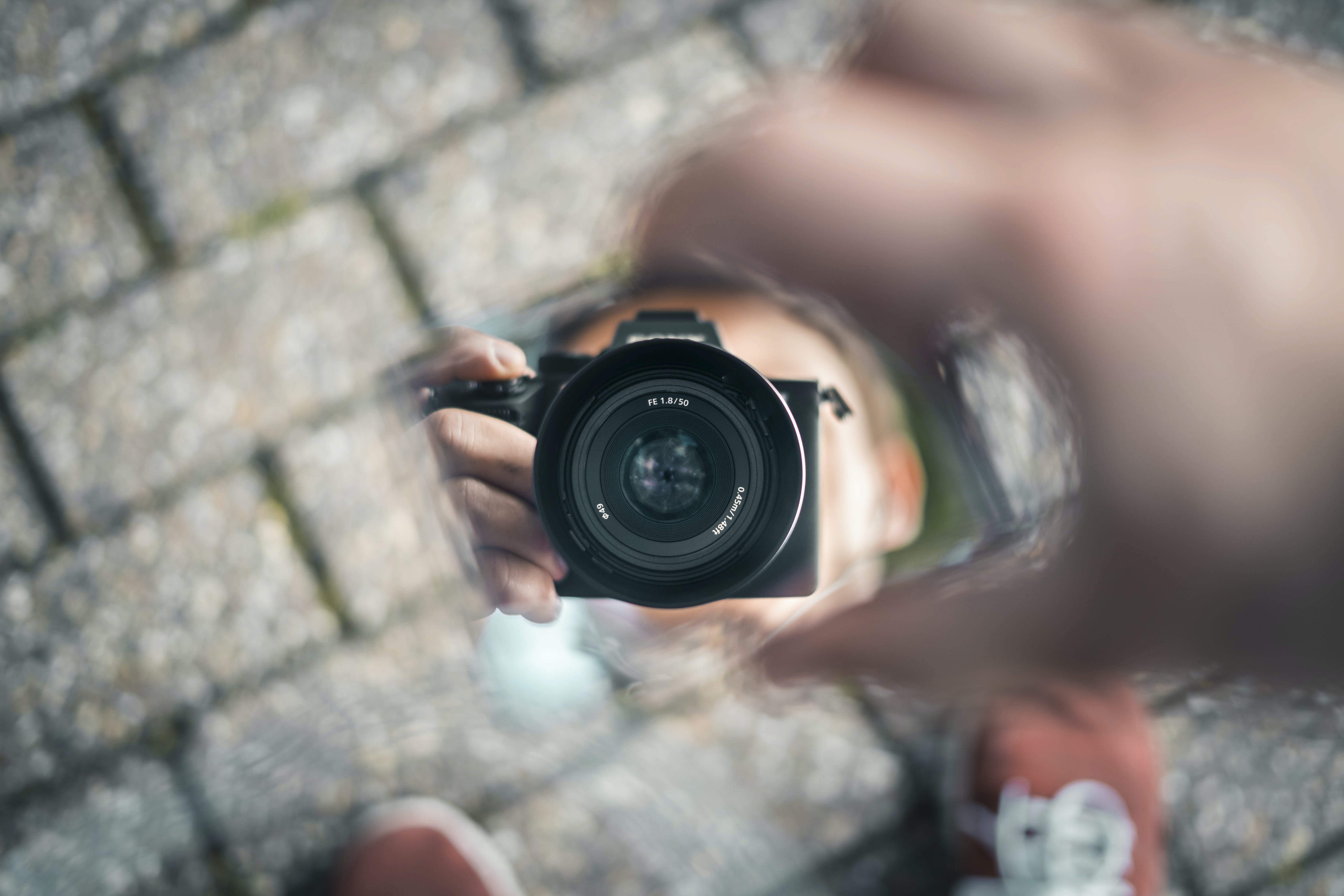 Selective Photo of Person Holds Black Dslr Camera