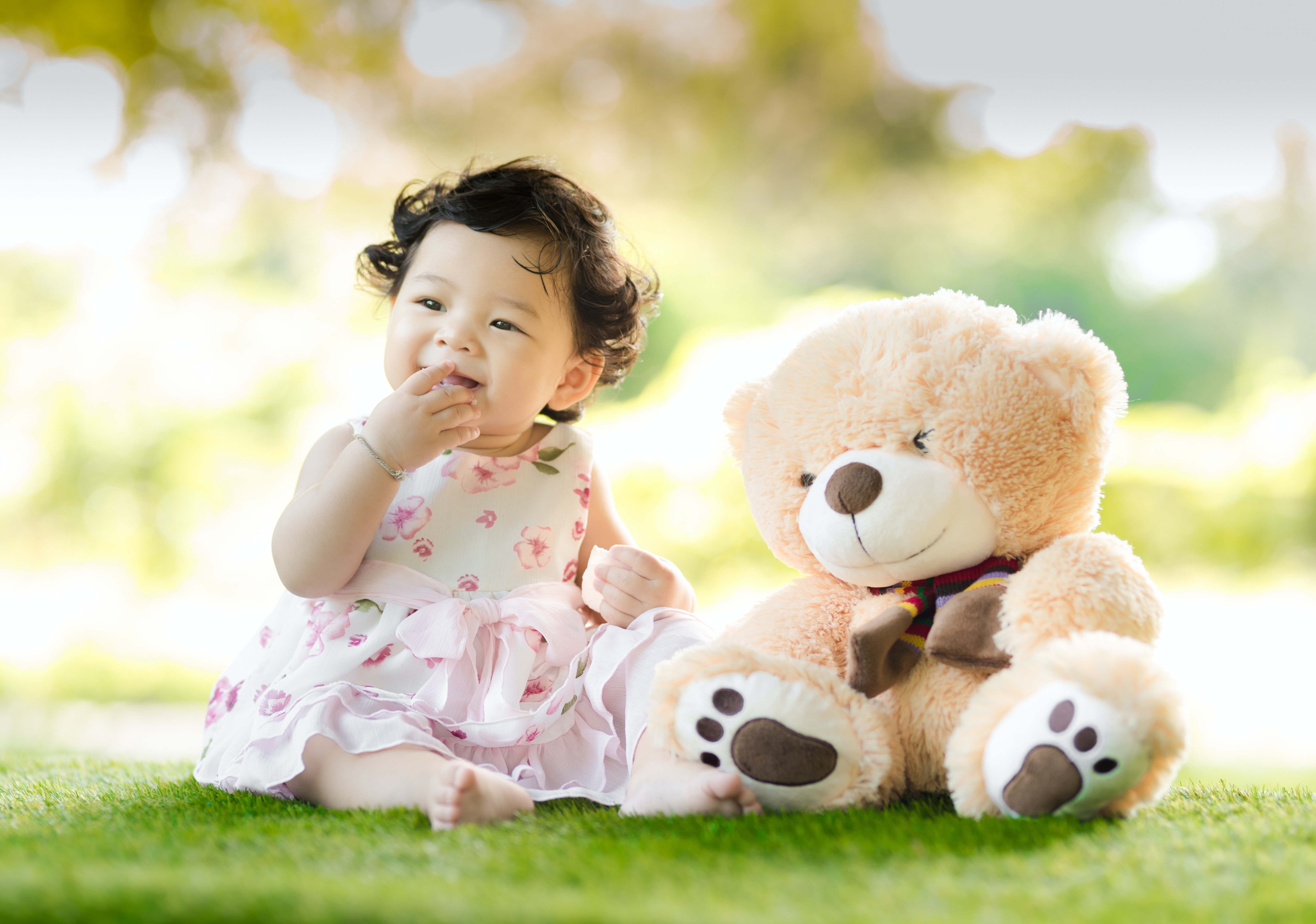 Baby sitting on green grass beside bear plush toy at daytime · free stock photo