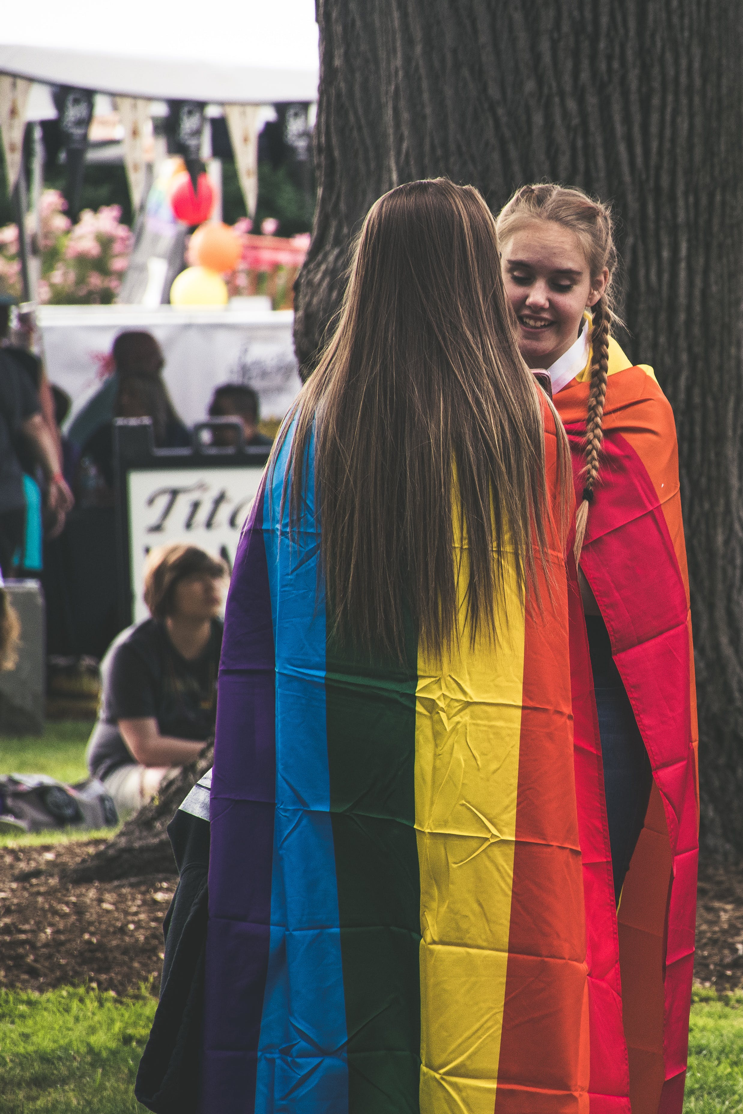Photo of Two Woman Wearing Rainbow Capes