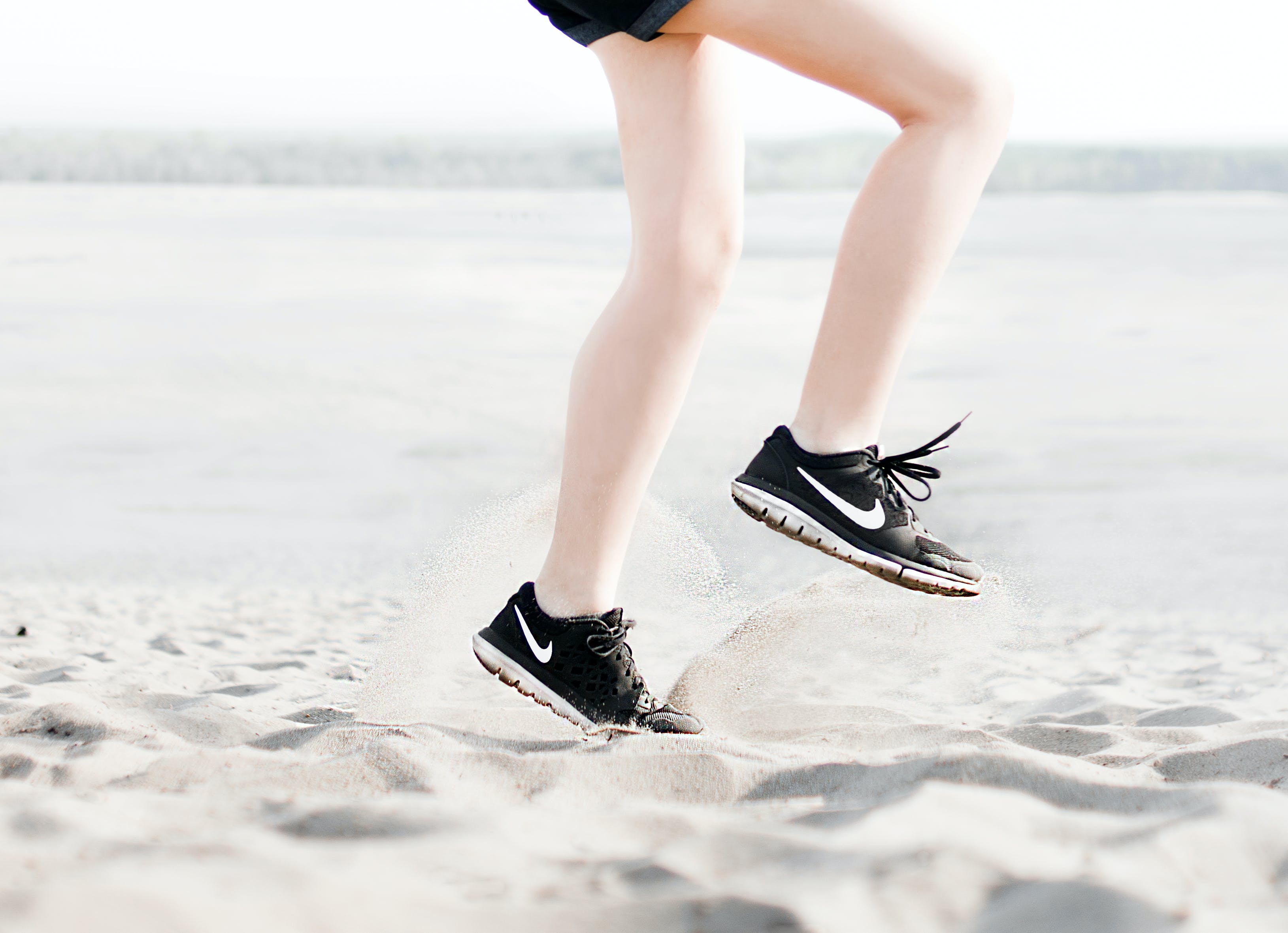 Photo of Woman Wearing Pair of Black Nike Running Shoes