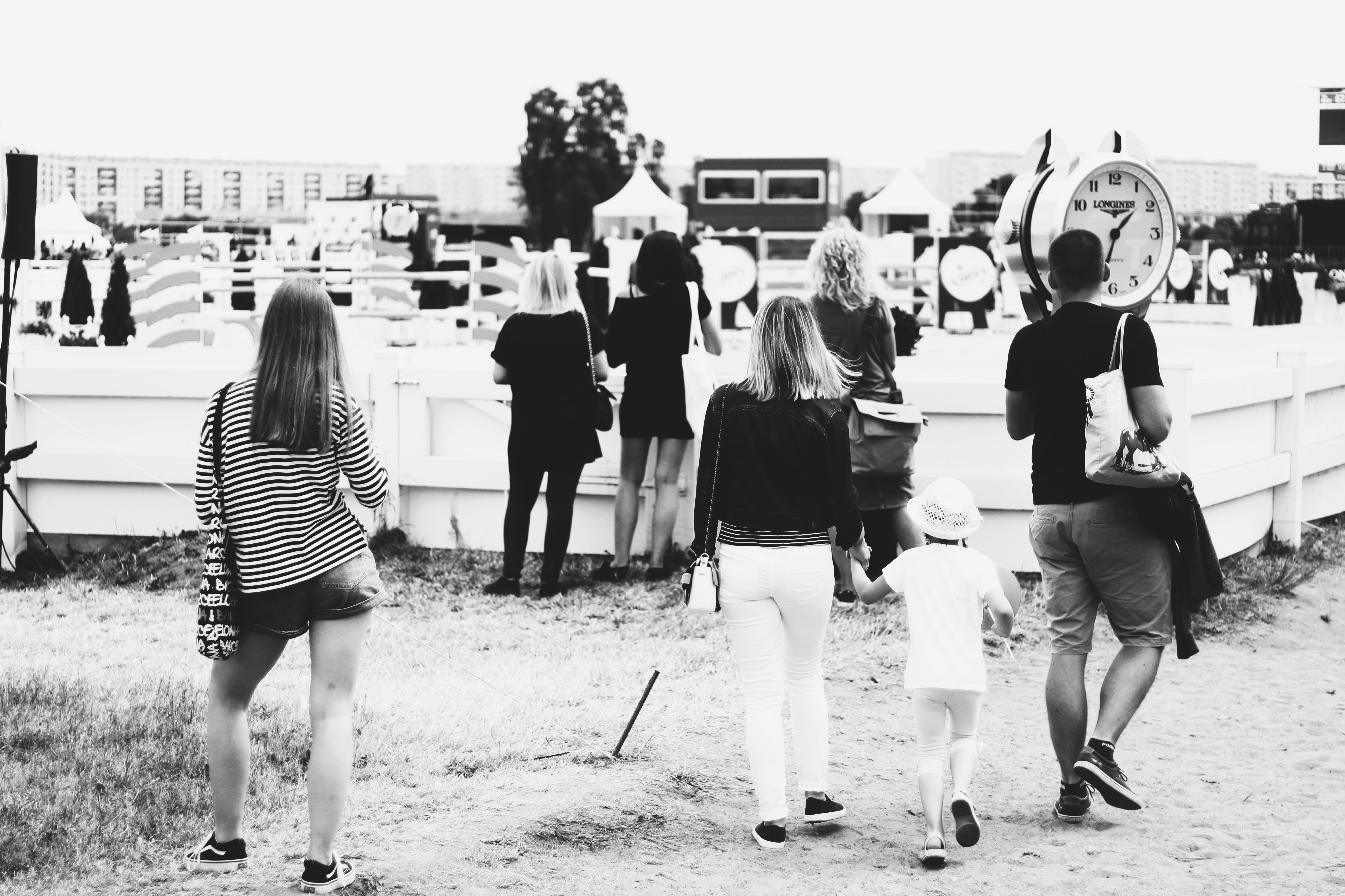 Grayscale Photo of People Gathering Near Clock