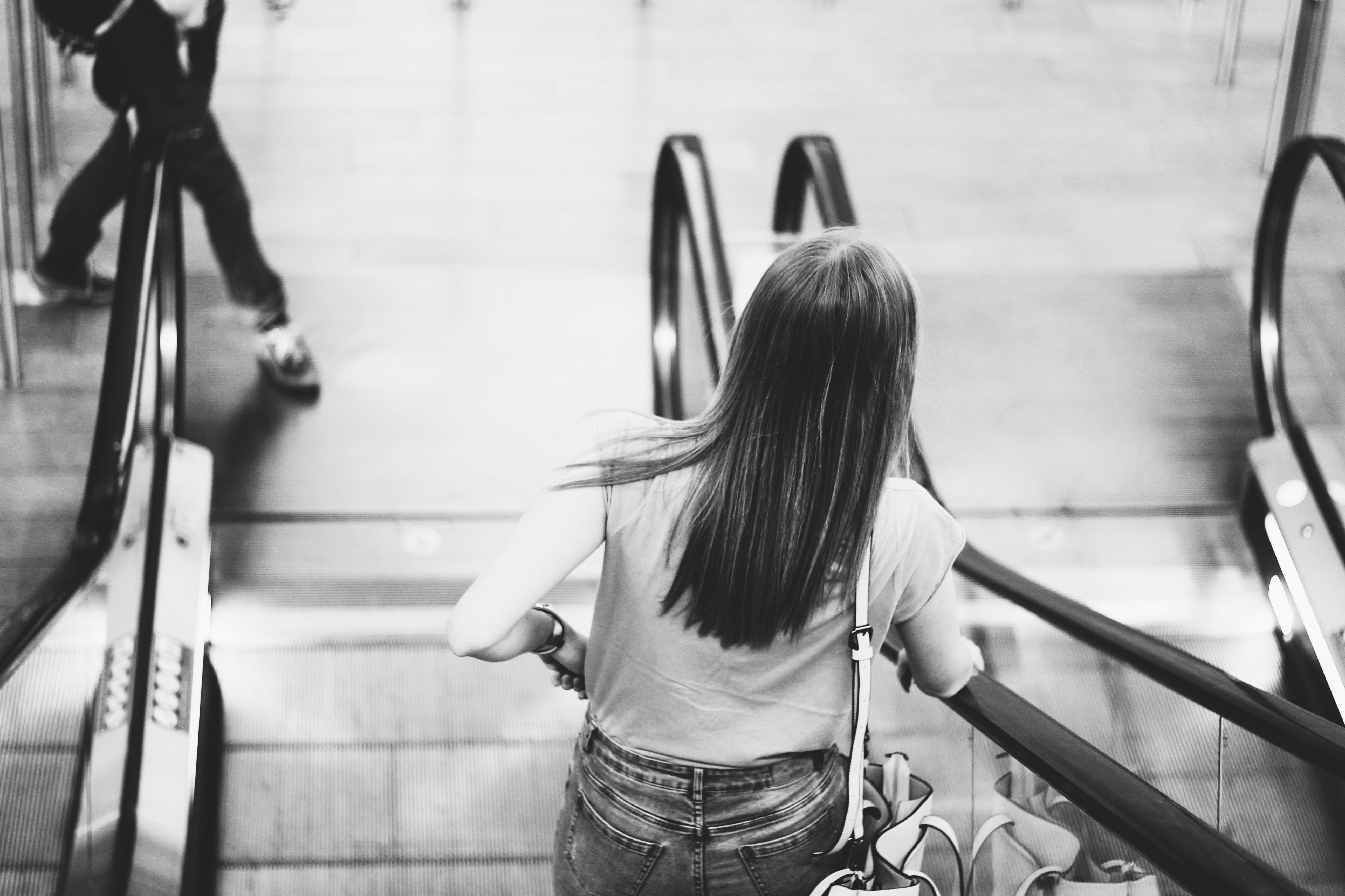Monochrome Photography of Woman on the Escalator