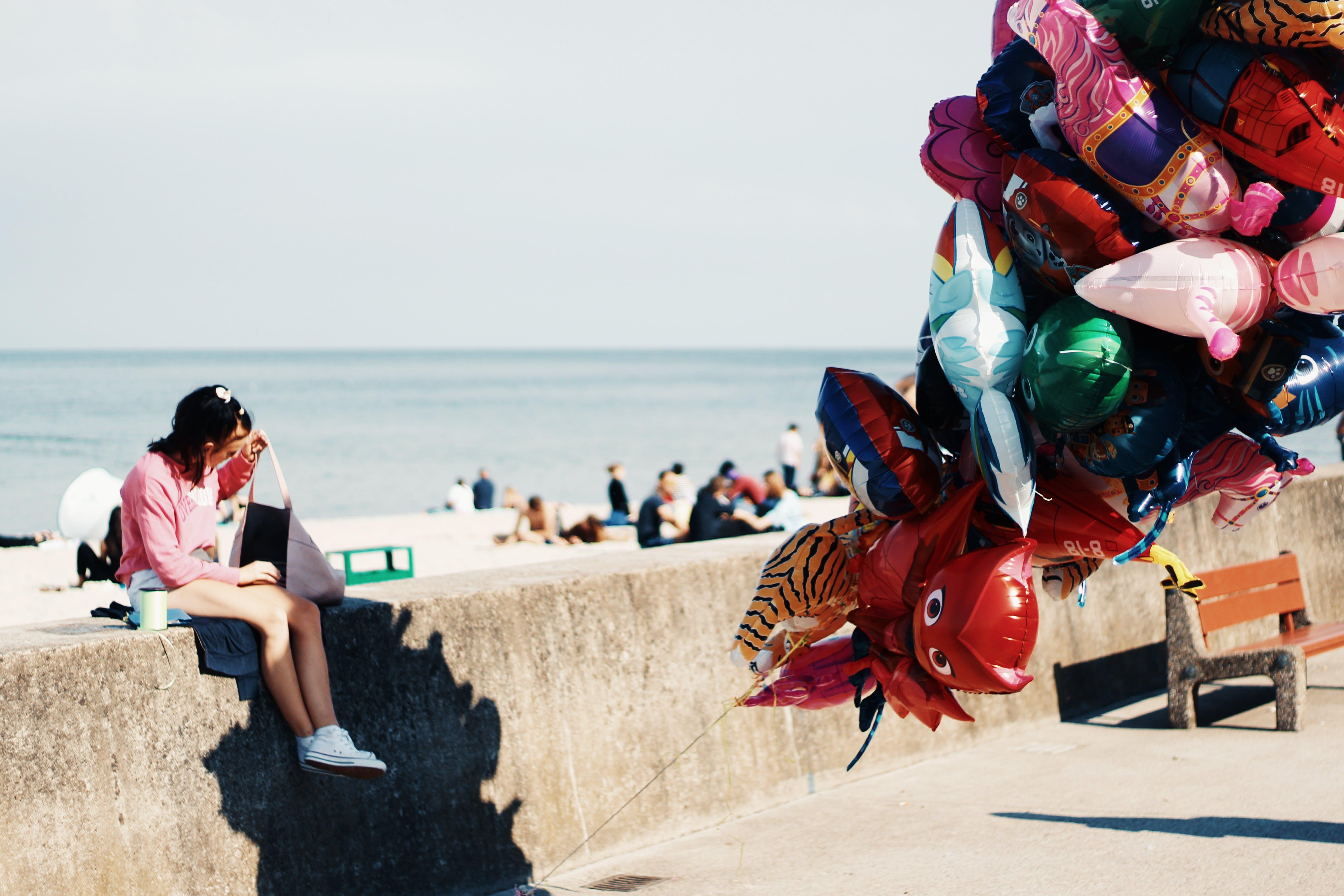 Woman Sitting on Gray Concrete Bench Next to Beach