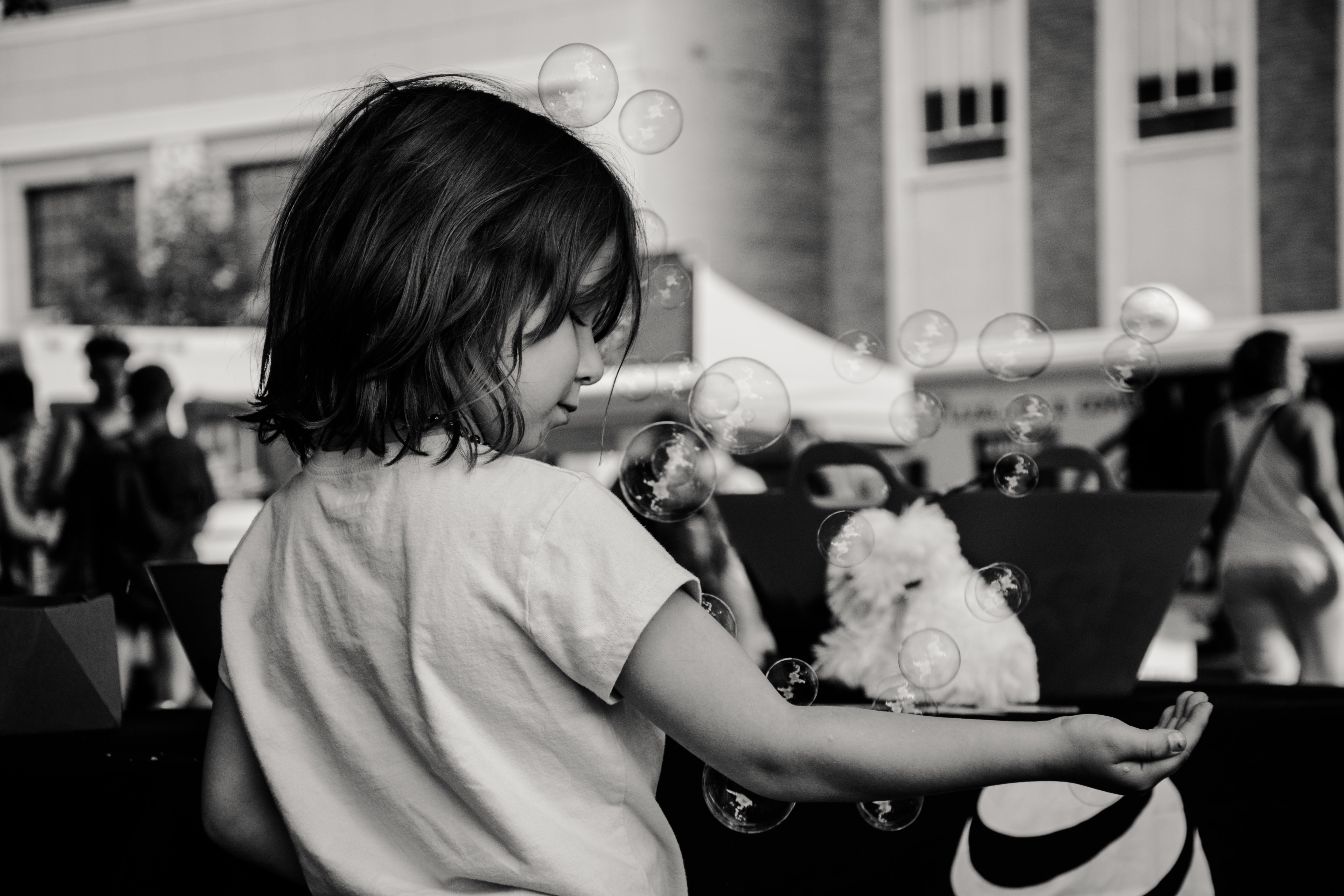 Monochrome Photography of Girl Playing With Bubbles