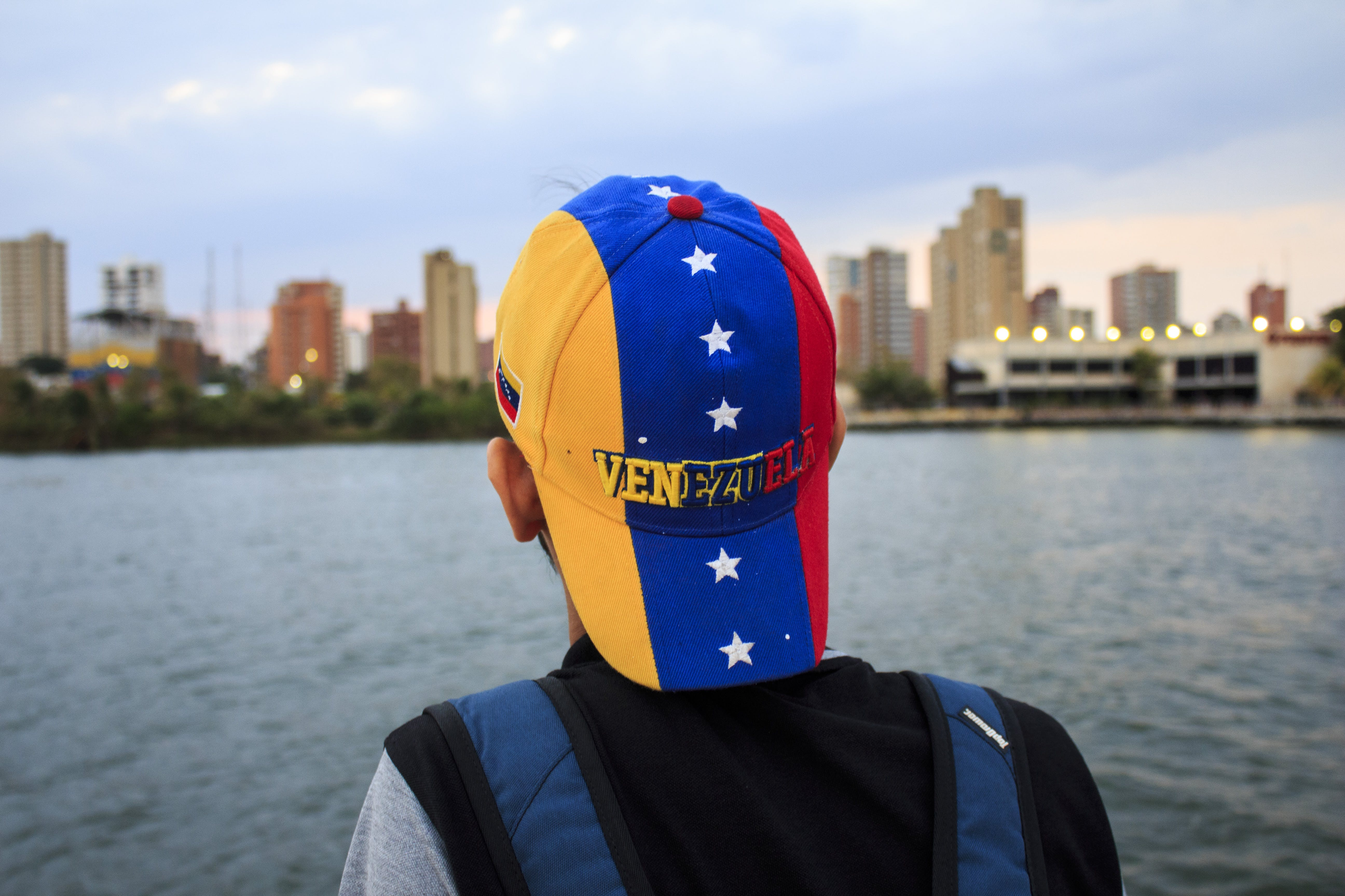 Person Wearing Black and Gray Shirt With Yellow, Blue, and Red Star Print Cap