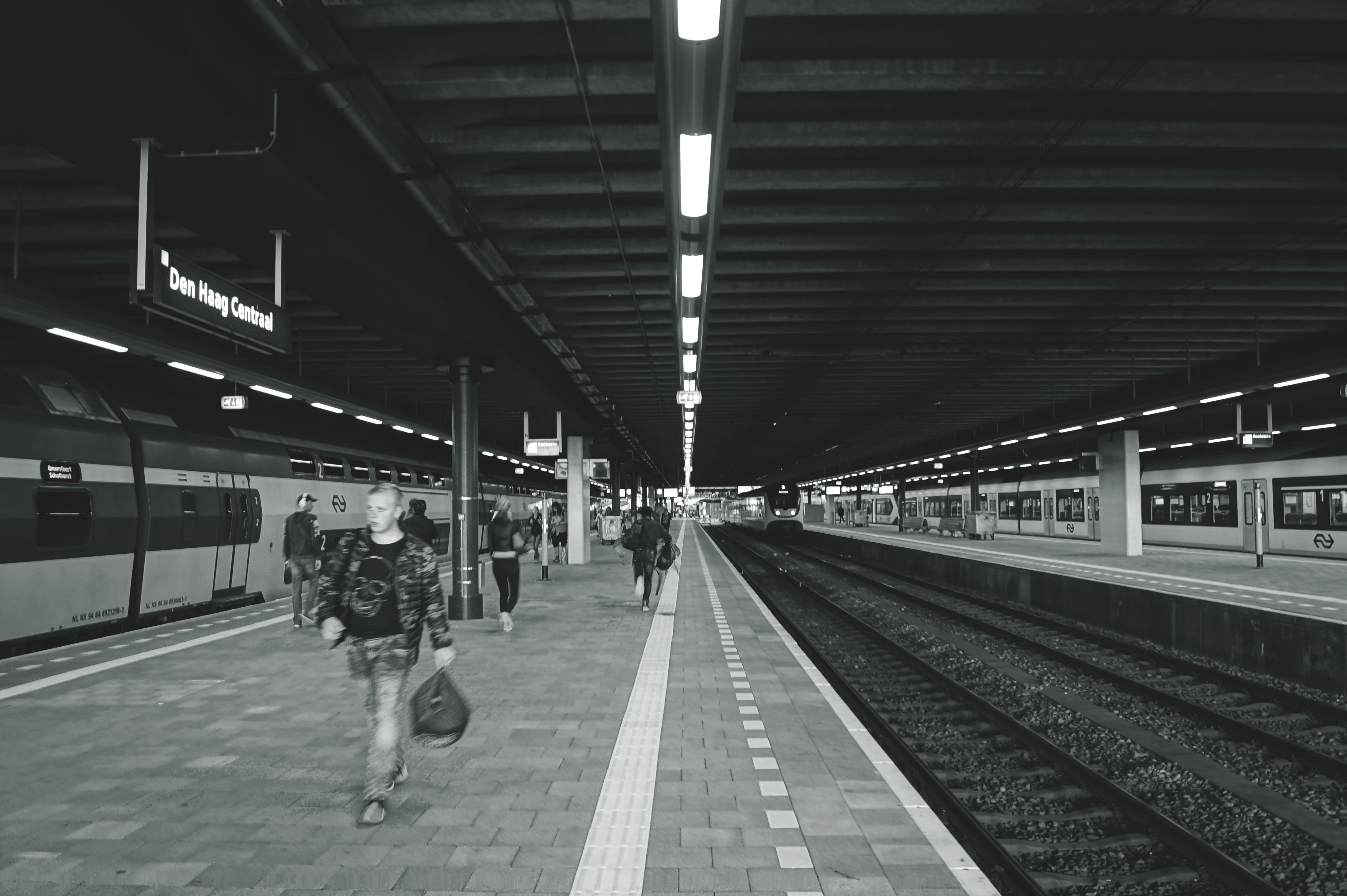 Grayscale Photography of Man Carrying Bag Walking on Subway Station